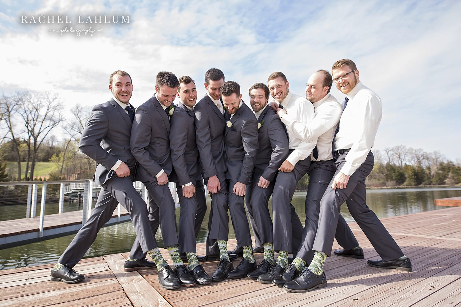 Groom and groomsmen show off their fish socks in Chaska, MN park.
