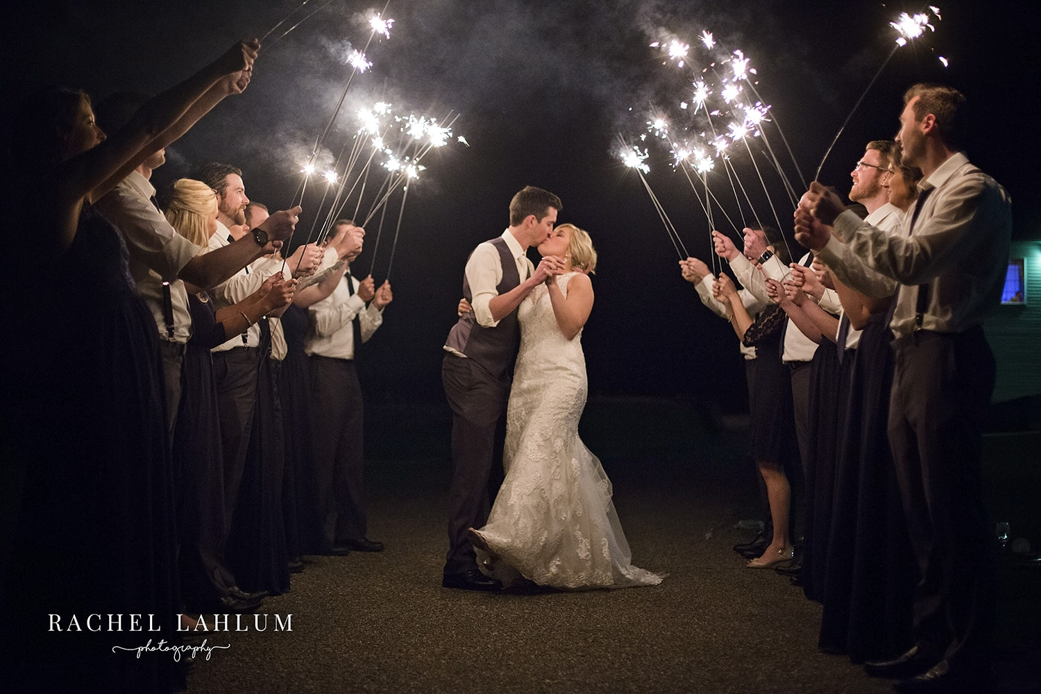 Bride and groom kiss during a sparkler exit in Jordan, MN
