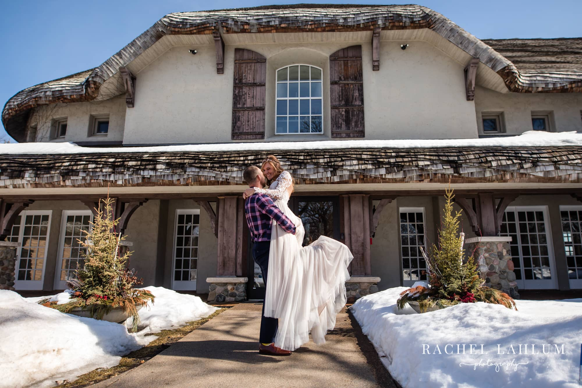 Baylor holds Jessa in front of their indoor wedding venue, Bavaria Downs.