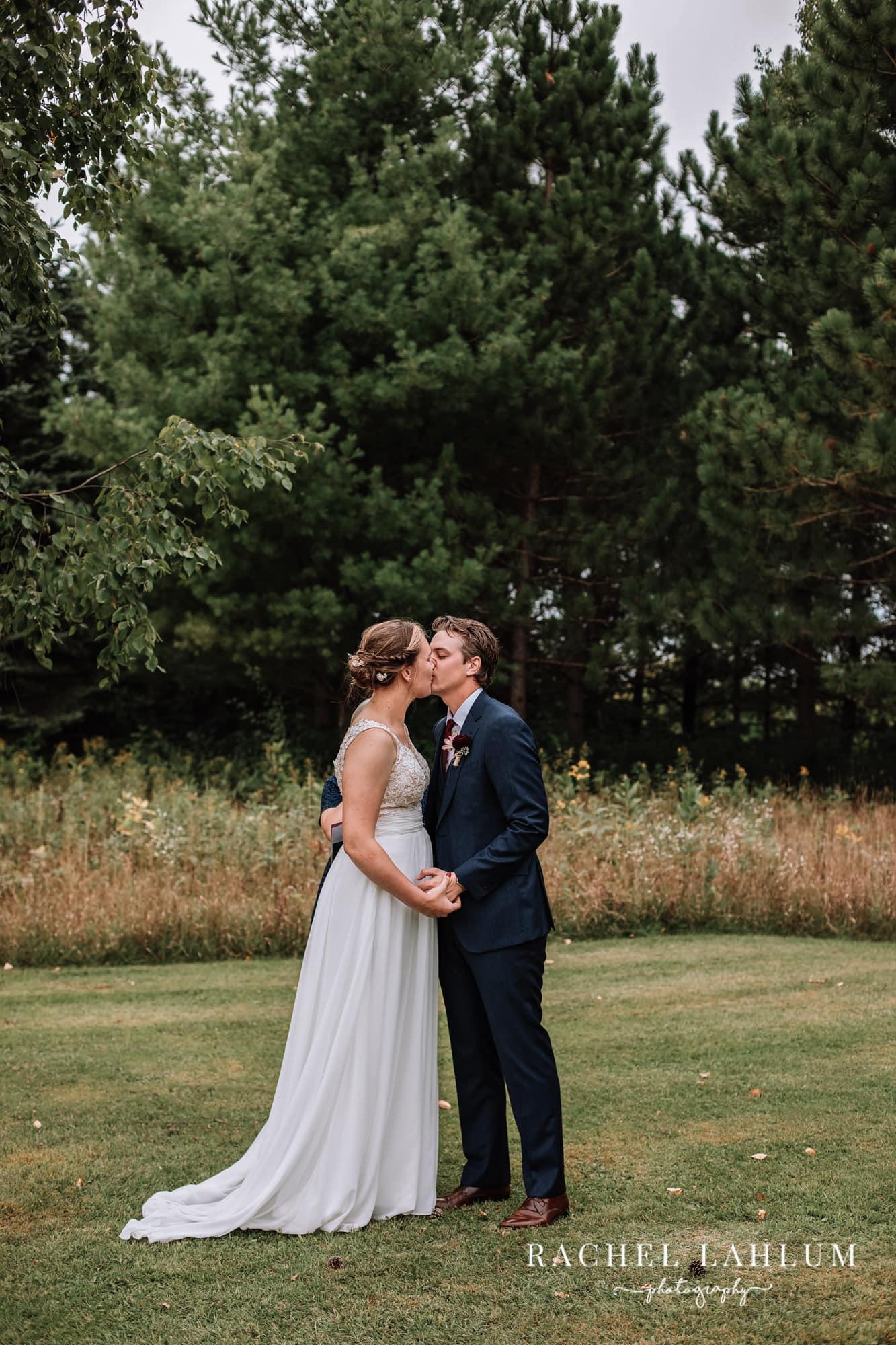 Portrait of bride and groom kissing in a field in Zimmerman, Minnesota.