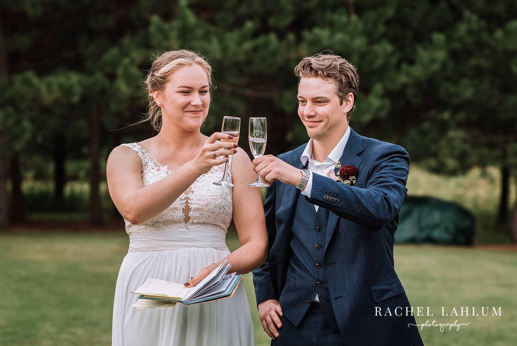 Bride and groom toast at their outdoor wedding.