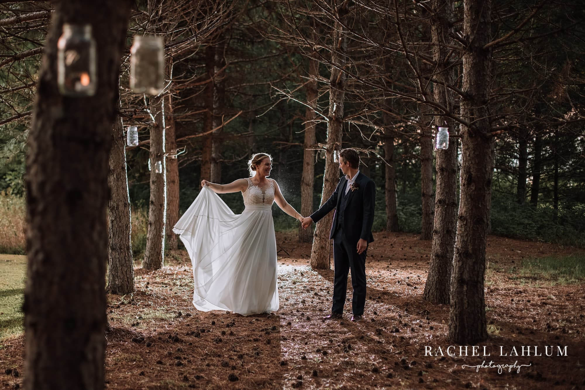 Bride and groom hold hands among pine trees and under candle-filled mason jars.