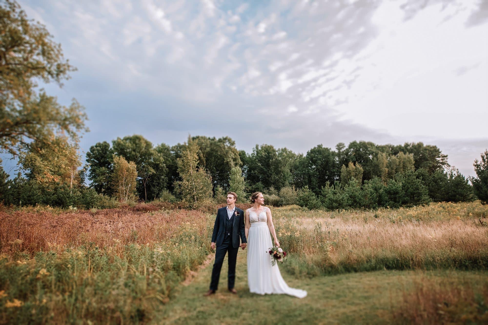 Bride and groom and stand holding hands on a trail in Zimmerman, Minnesota.