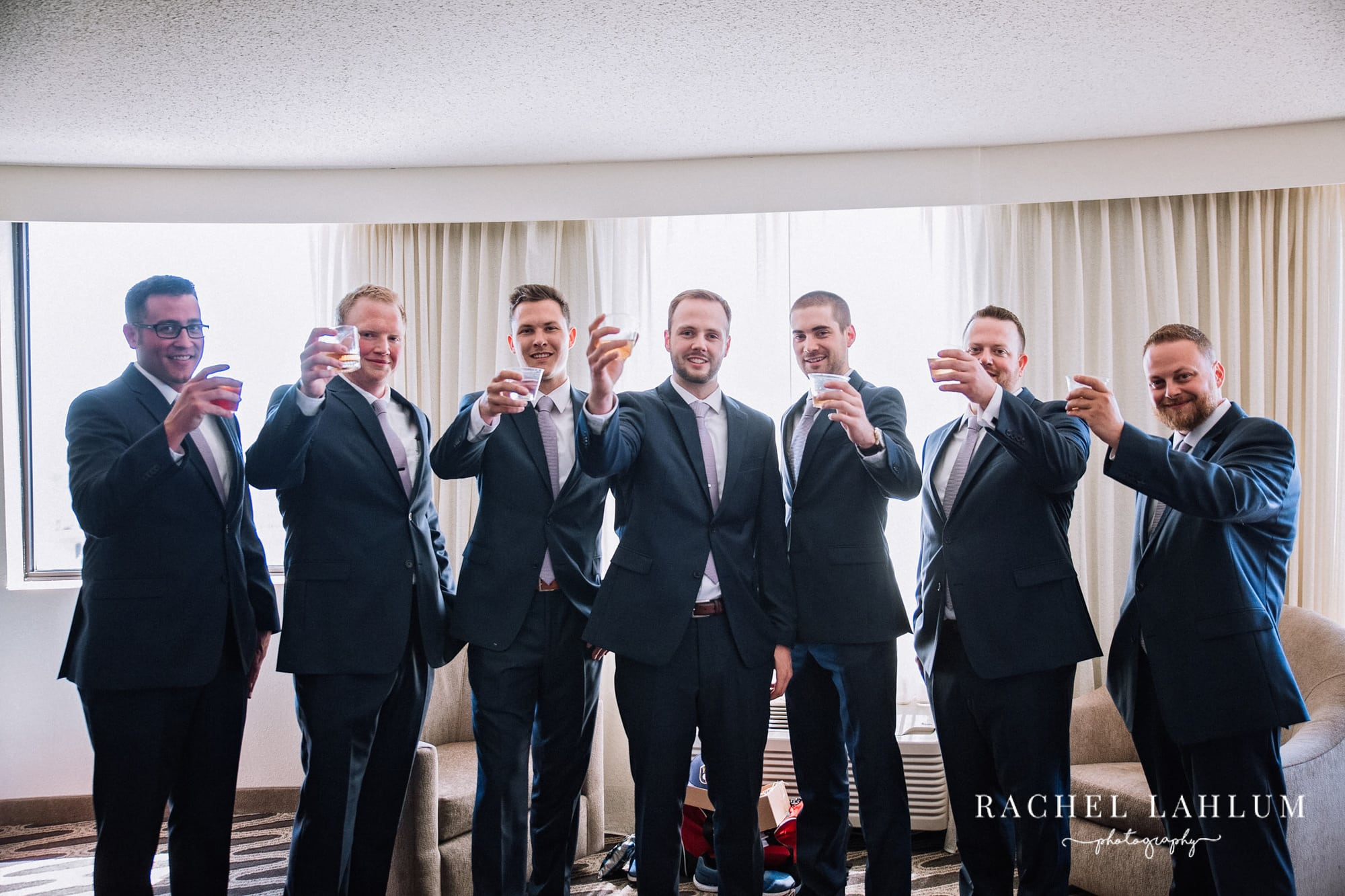 Groom surrounded by groomsmen making a toast with whiskey glasses.