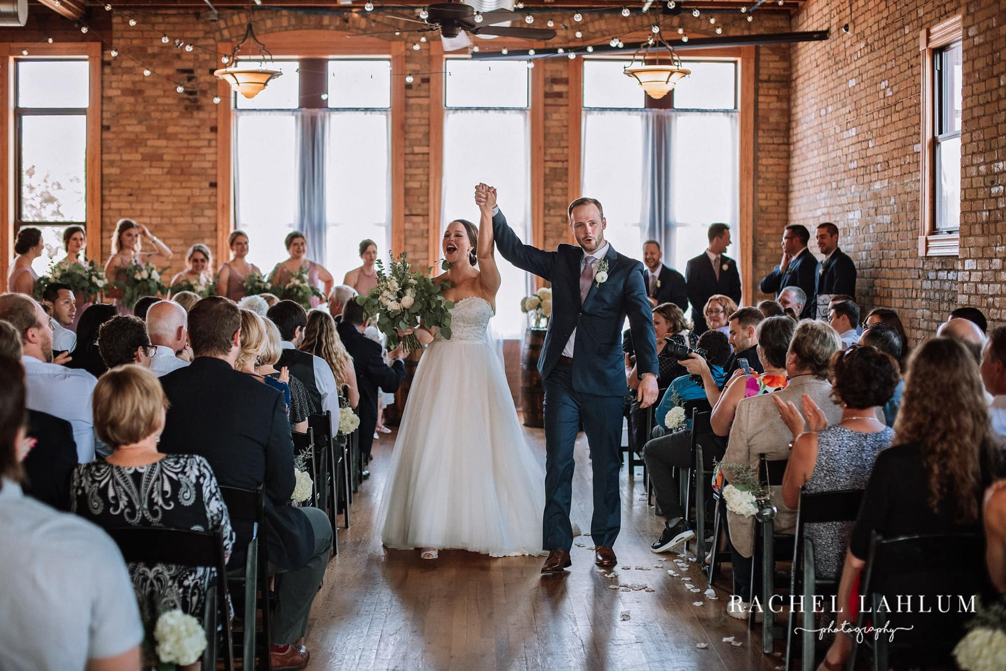 Bride and groom celebrate and walk down aisle at Day Block Event Center.