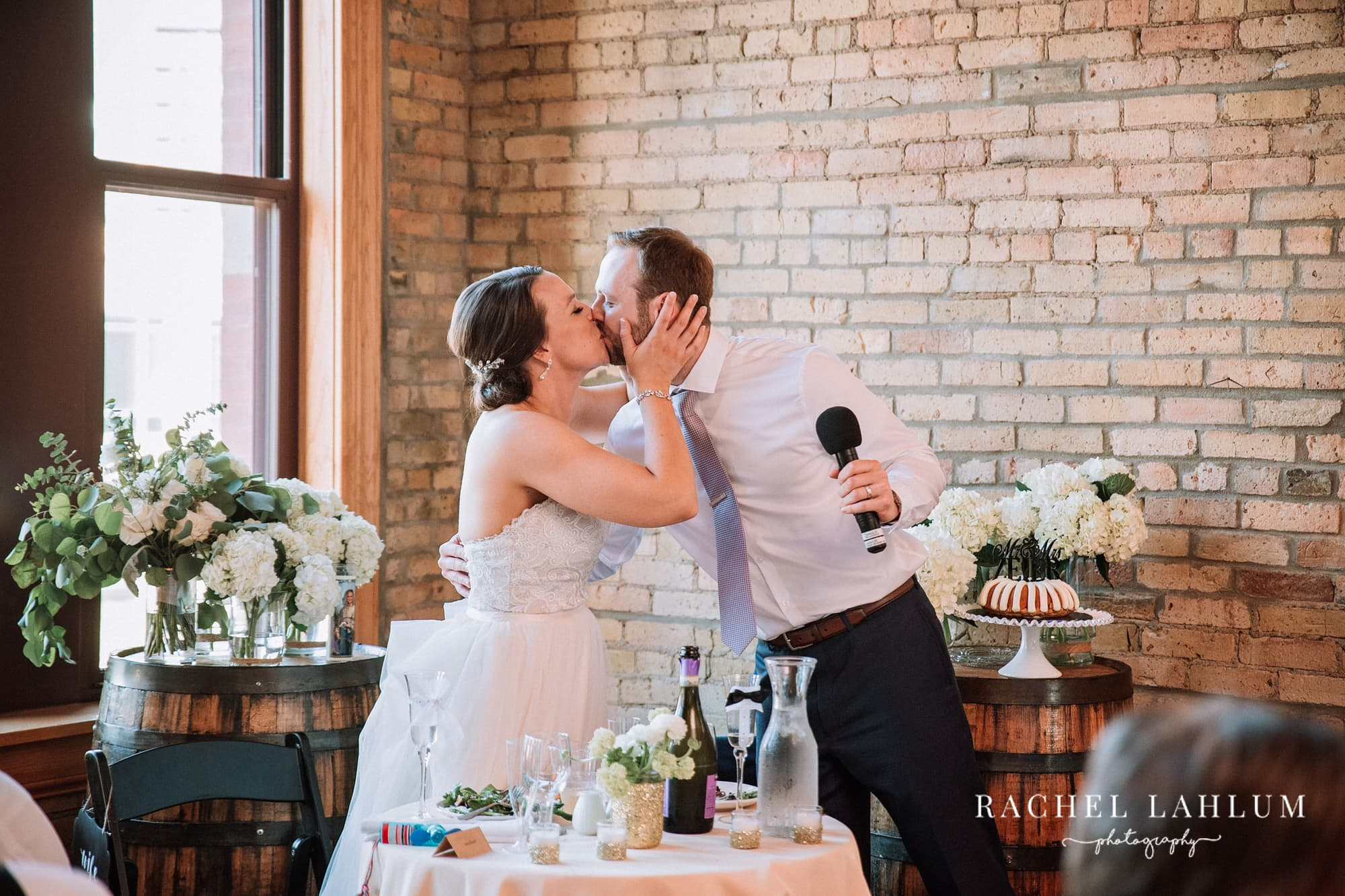 Bride and groom kiss after a speech at Day Block Event Center.