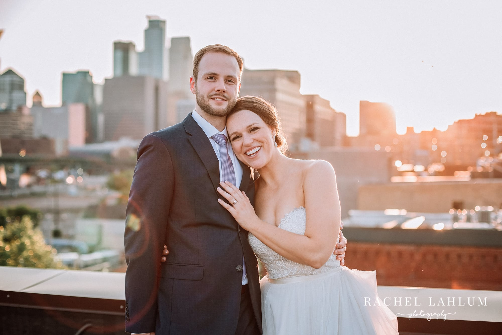 Wedding portrait in front of Minneapolis skyline at sunset.