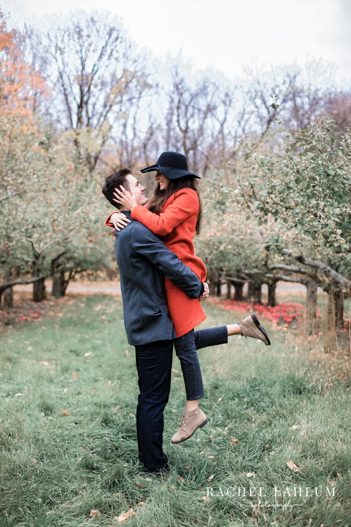 Man picks up fiancee in apple orchard during proposal photography session.