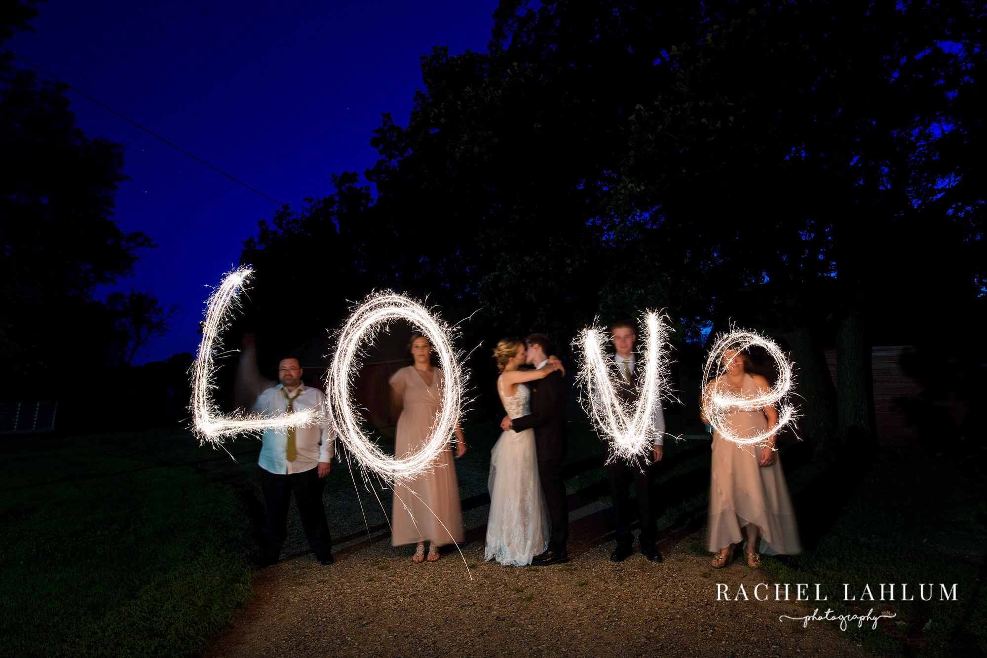 Wedding guests light painting the word love with sparklers.