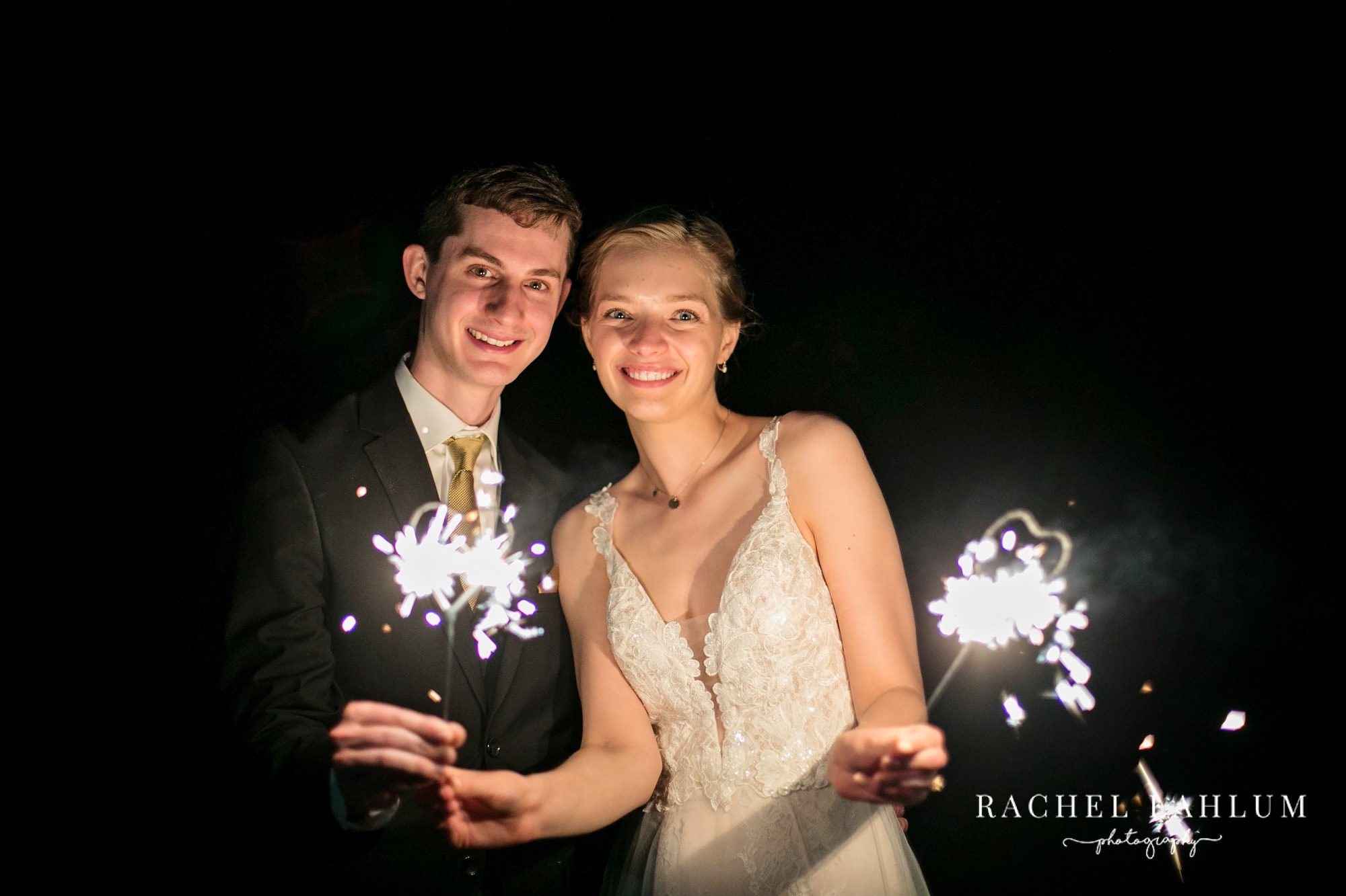 Newlywed couple holds sparklers.