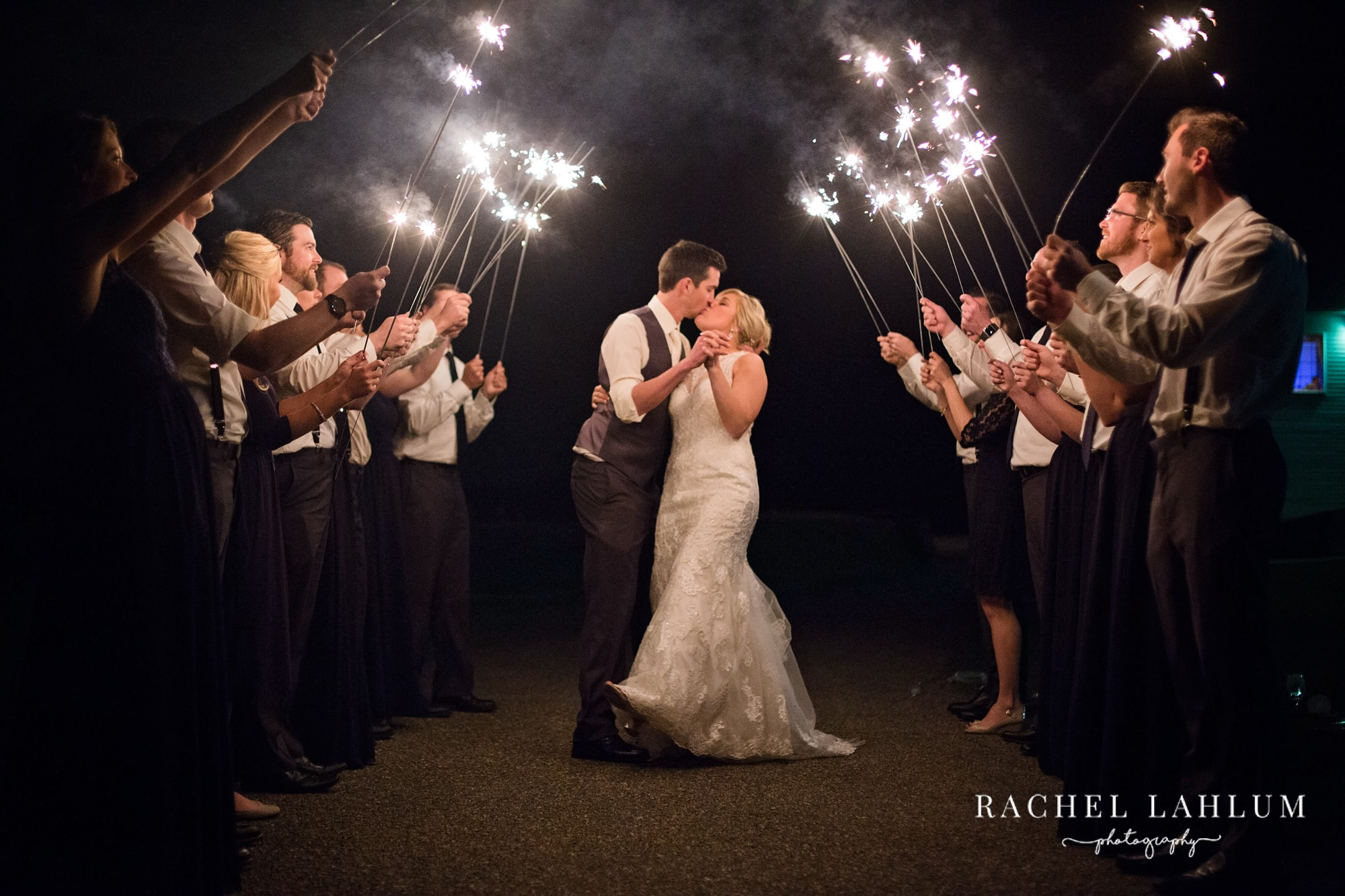 Groom dips and kisses bride under tunnel of wedding sparklers.