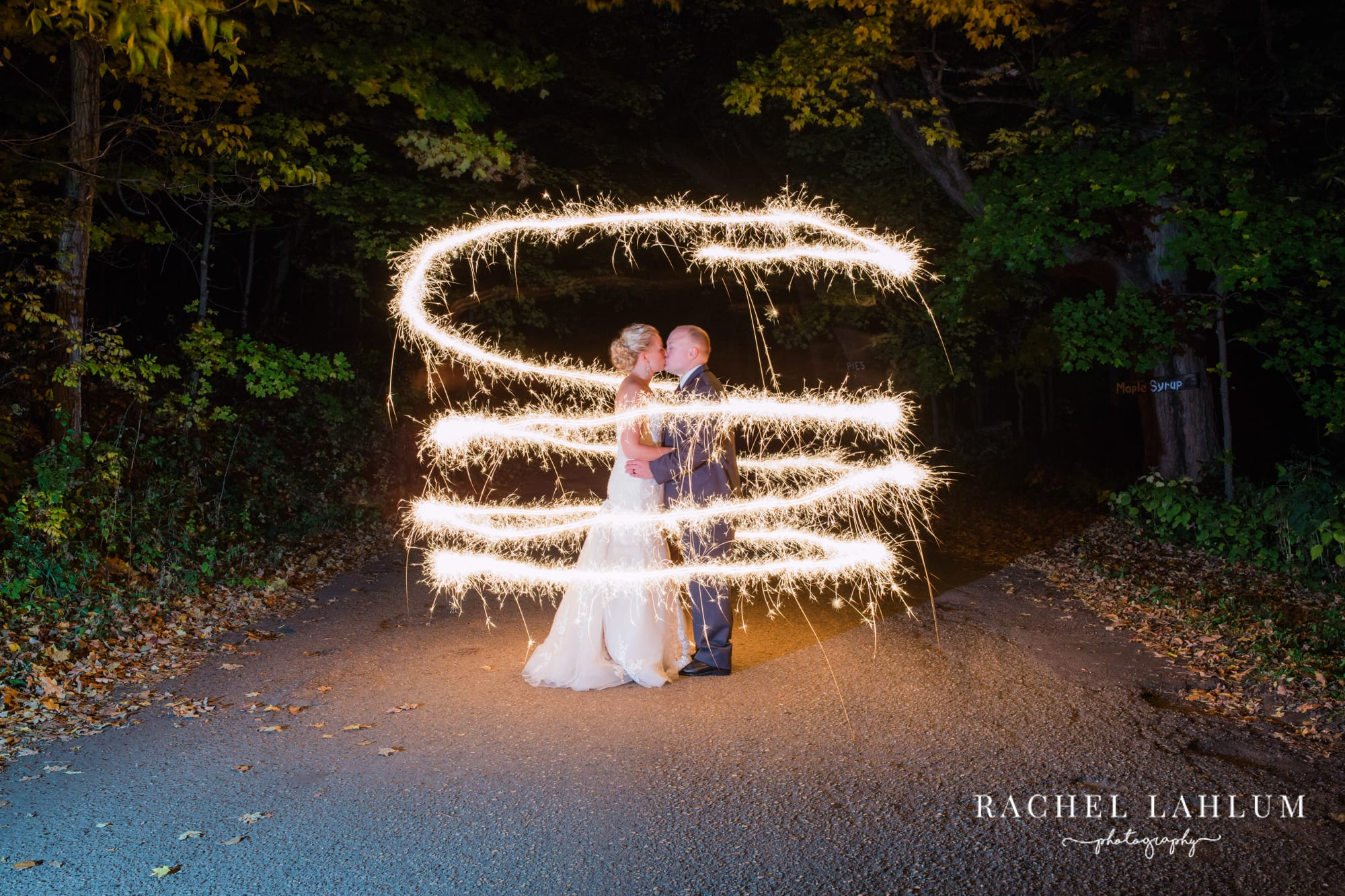 Bride and groom kiss in the swirl of sparklers.