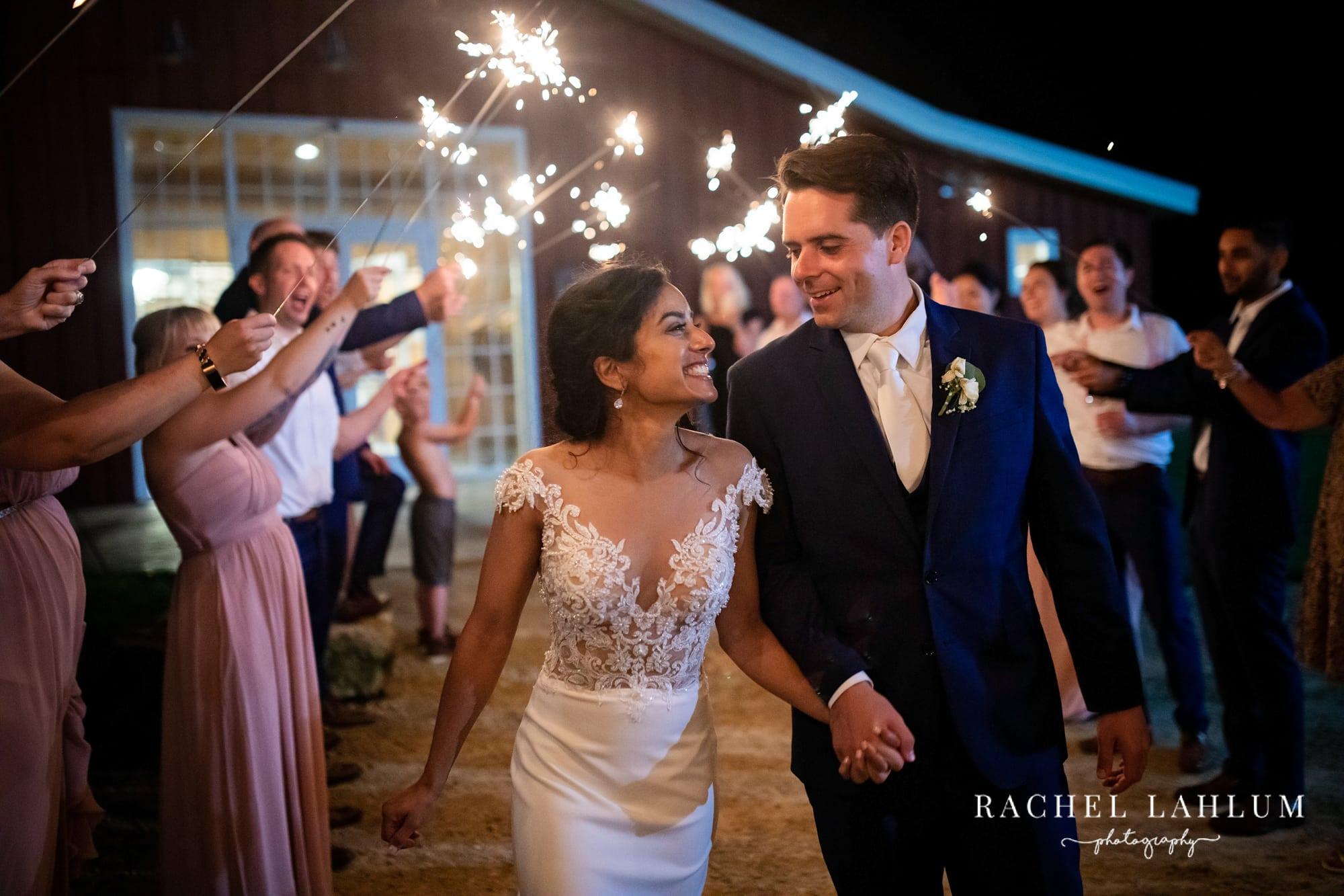 Bride and groom walk through sparkler tunnel.