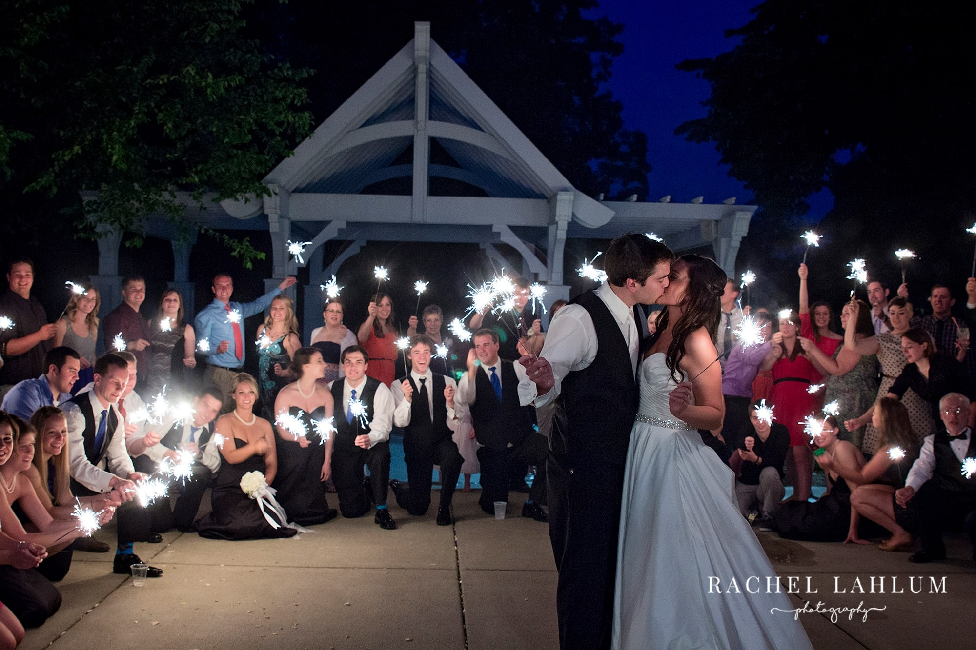 Bride and groom kiss in front of wedding party holing sparklers.