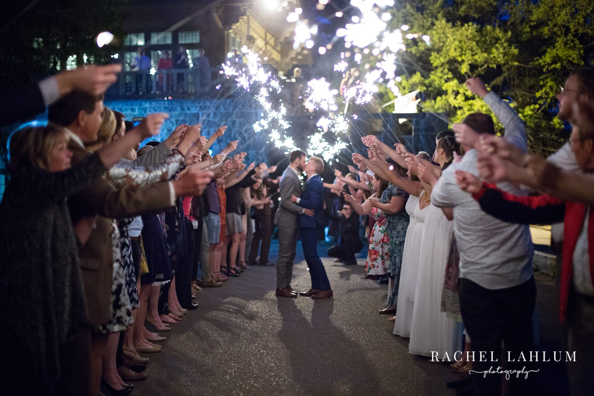 Newlyweds embrace and kiss under a sparkler tunnel.