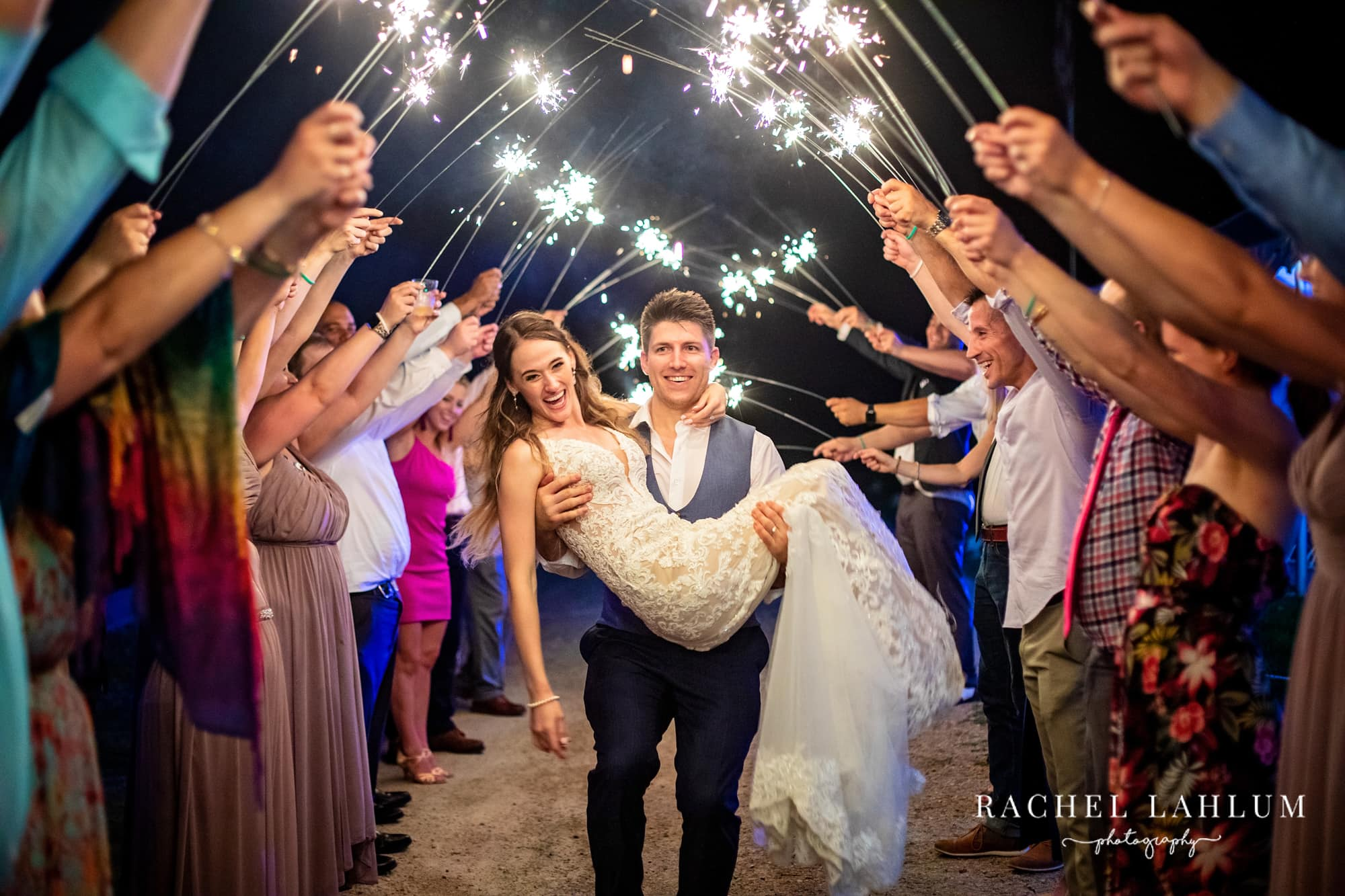 Groom carries bride through tunnel of sparklers.
