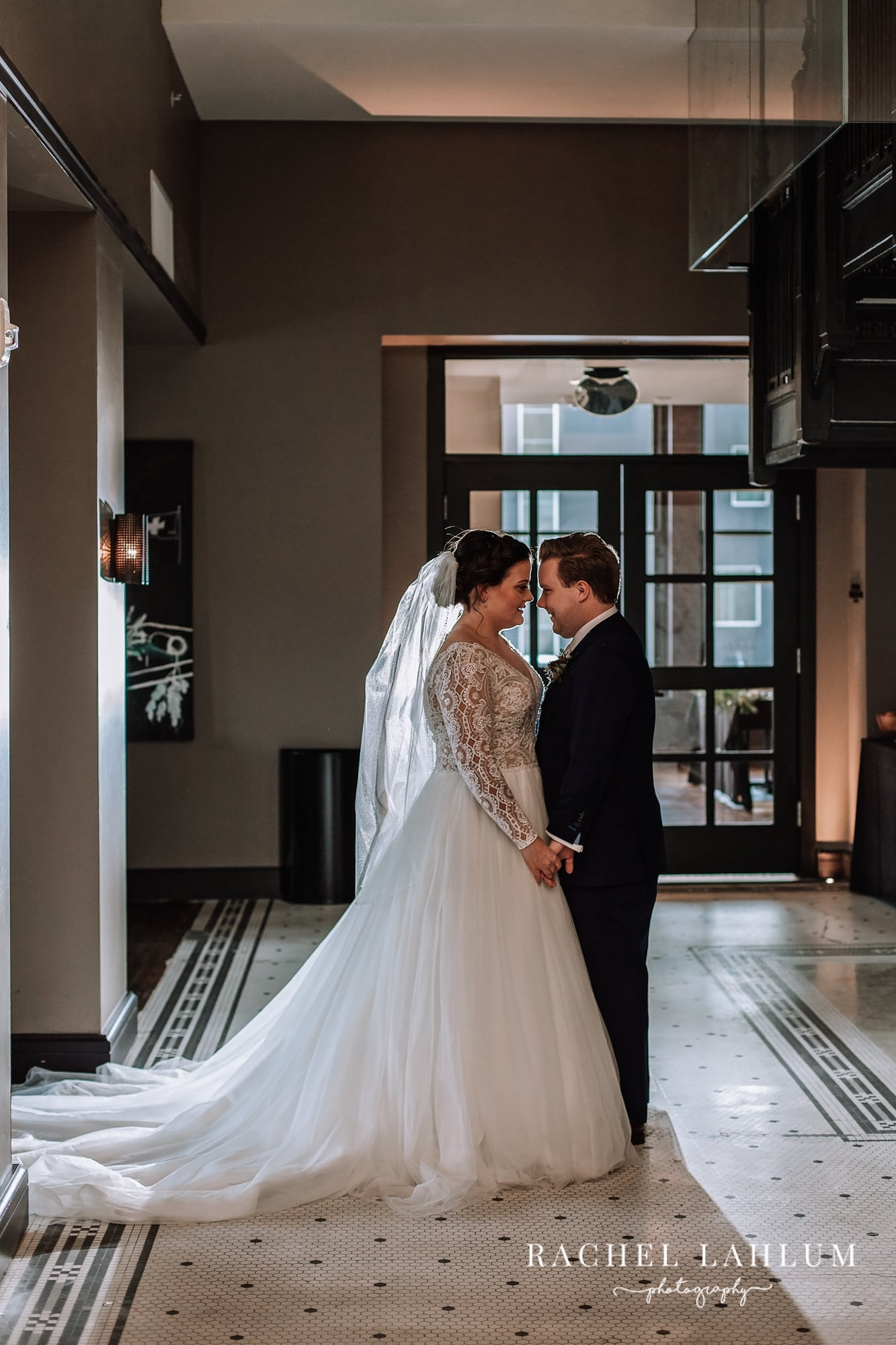 Bride and groom pose for intimate portrait in the lobby of Surety Hotel in Des Moines, Iowa.
