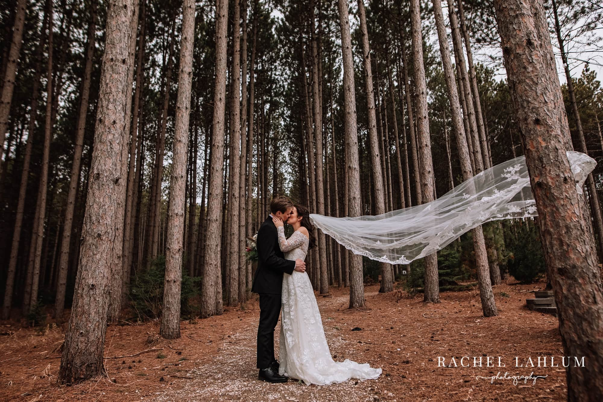 Bride and groom kiss in the woods after wedding at Pinewood Weddings and Events in Cambridge, Minnesota.