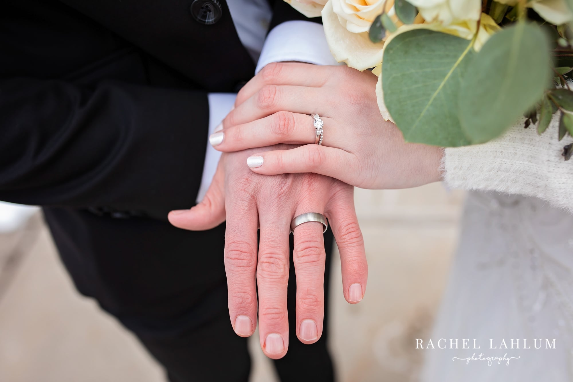 Bride and groom show their wedding rings.