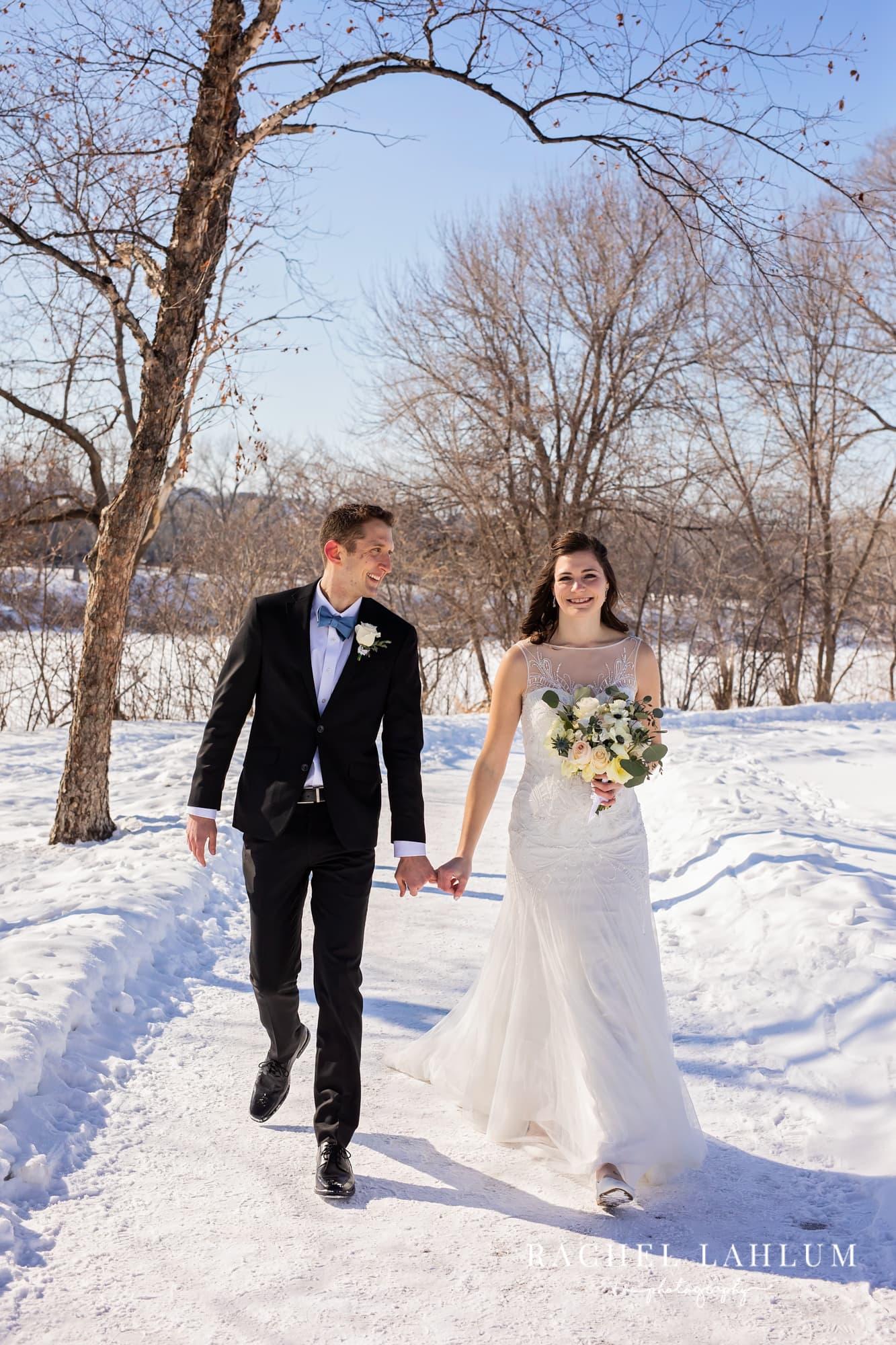 Bride and groom walk down a trail on Boom Island Park in Minneapolis, Minnesota.
