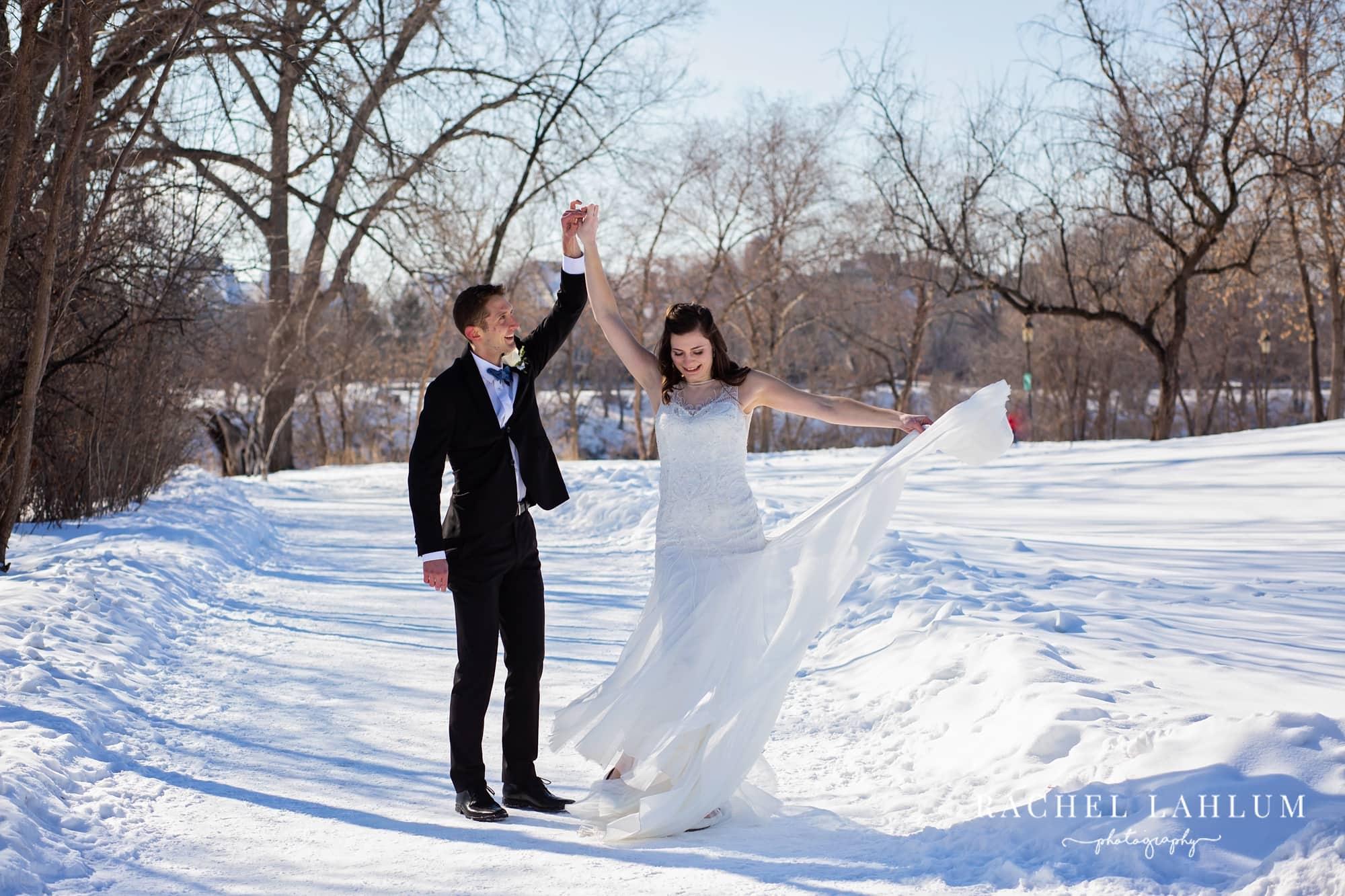Groom twirls bride on Boom Island Park in Minneapolis, Minnesota.
