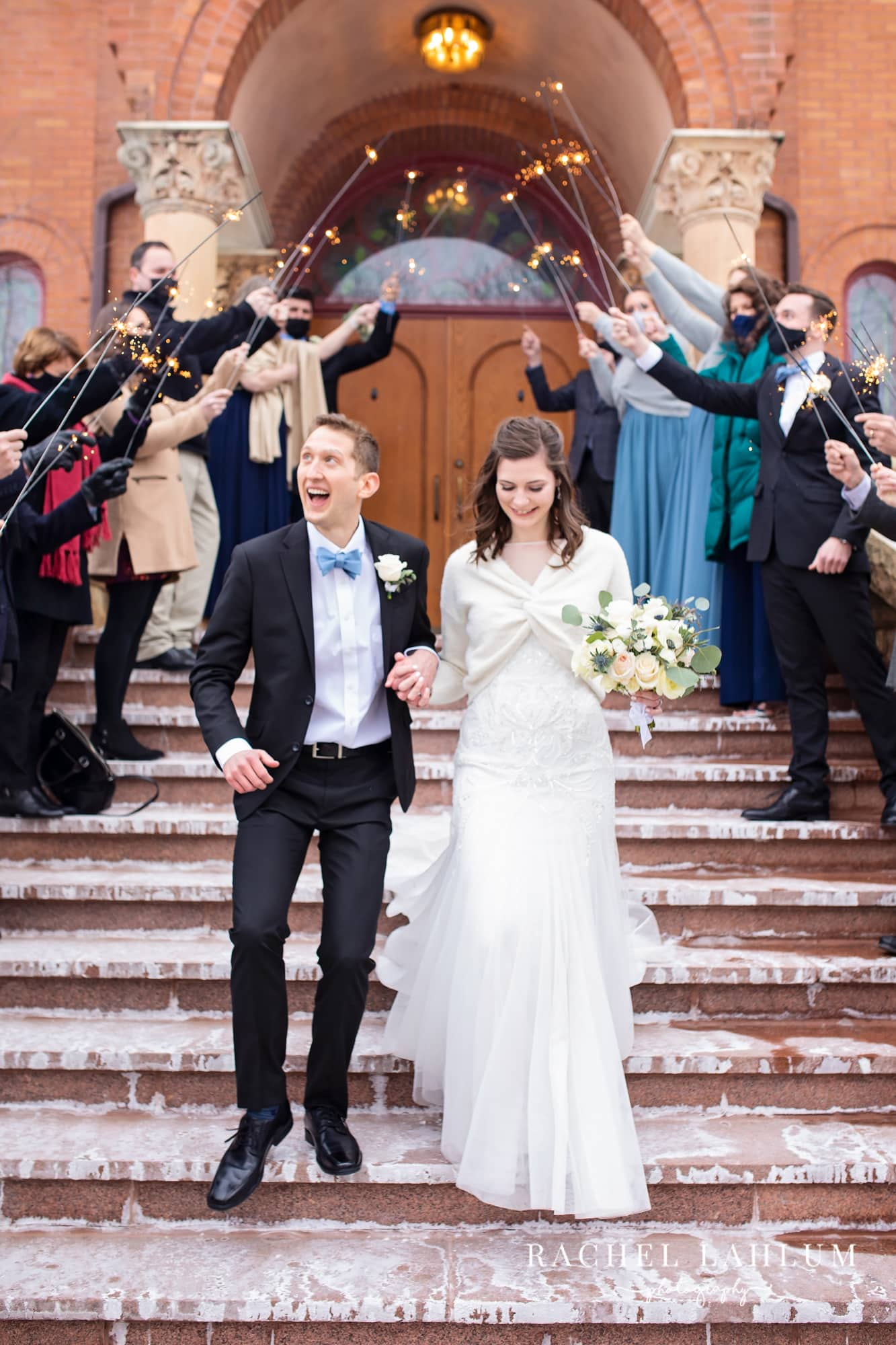 Bride and groom pose under a sparkler tunnel in front of St. Mary's Orthodox Cathedral.