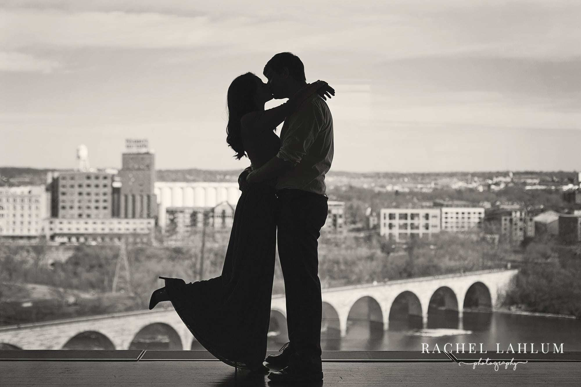 Couple kissing while silhouetted against the stone arch bridge in Minneapolis, MN. Taken from the Guthrie Theater in Downtown Minneapolis.