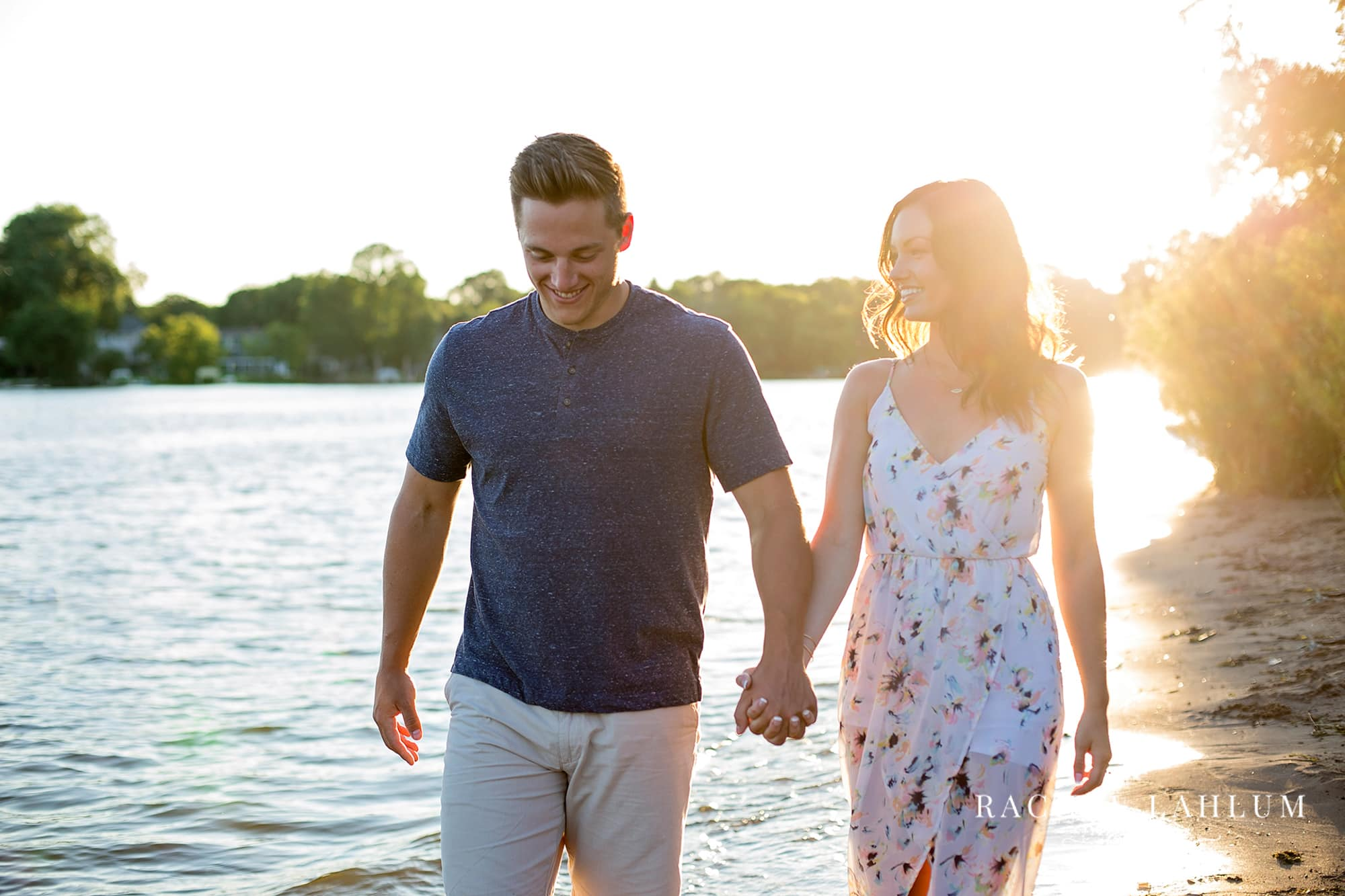 Engagement session couple walking along the lakeside beach at sunset in Minnesota.
