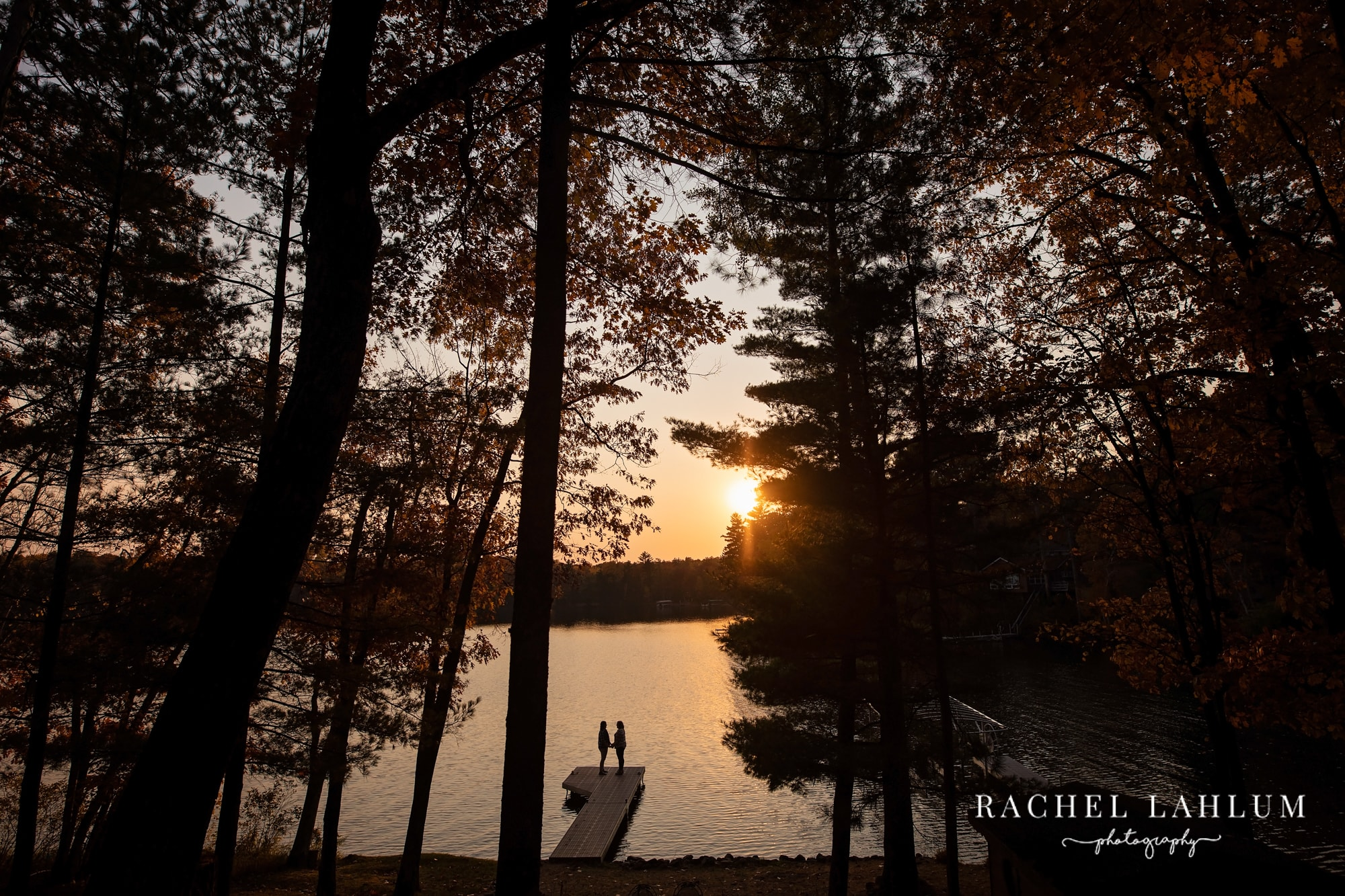 Same-sex couple holds hands at sunset for engagement session at the lake in Hayward, WI.