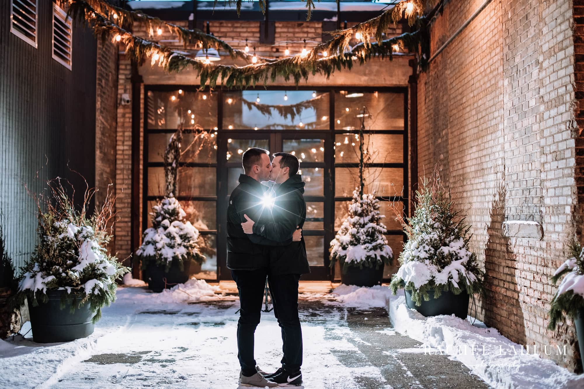 Couple holds a kiss during a winter night photo session at the Hewing Hotel in Downtown Minneapolis, MN.