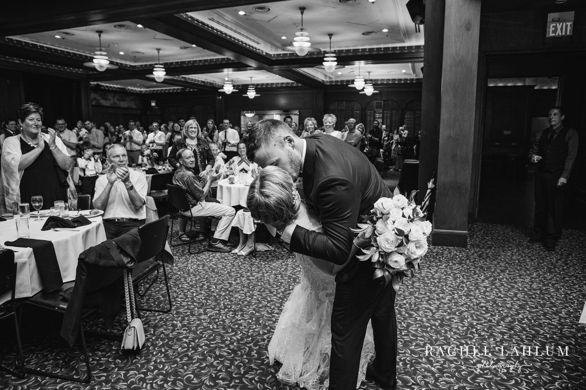 Groom dips and kisses bride during reception at The Metropolitan Club & Ballroom in Golden Valley, Minnesota.