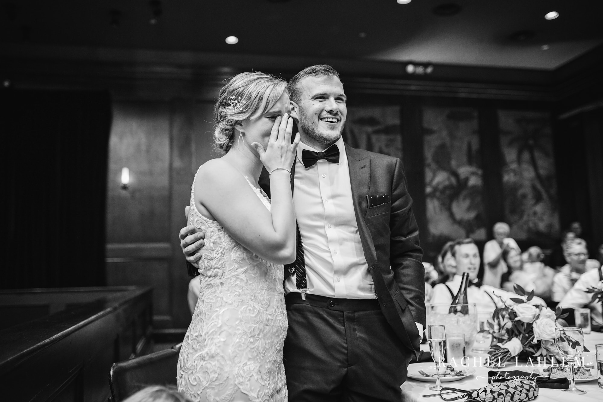 Groom embraces bride as she sheds tears during Golden Valley wedding reception.