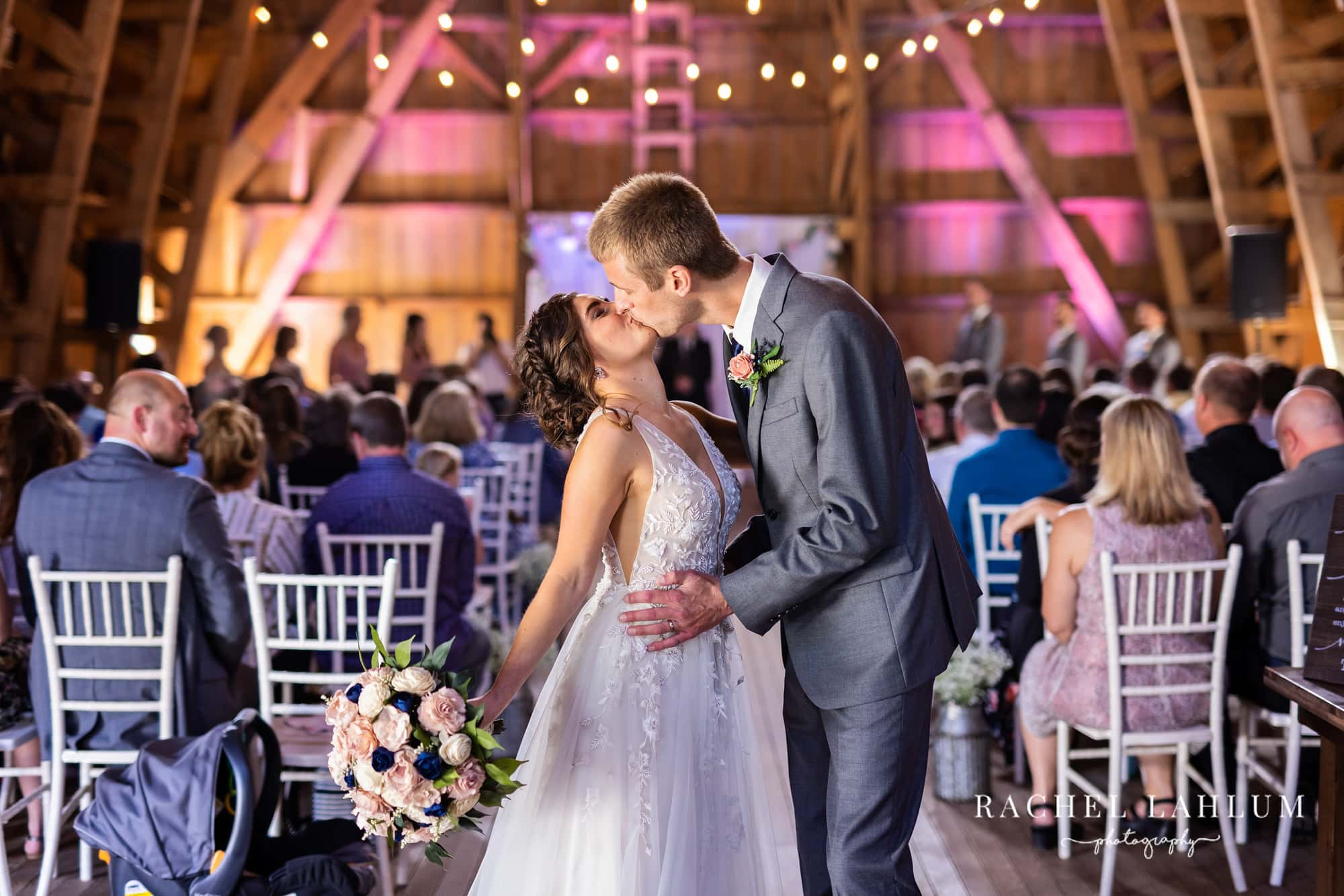 Bride and groom kiss in the barn loft aisle after ceremony at the Cottage Farmhouse.