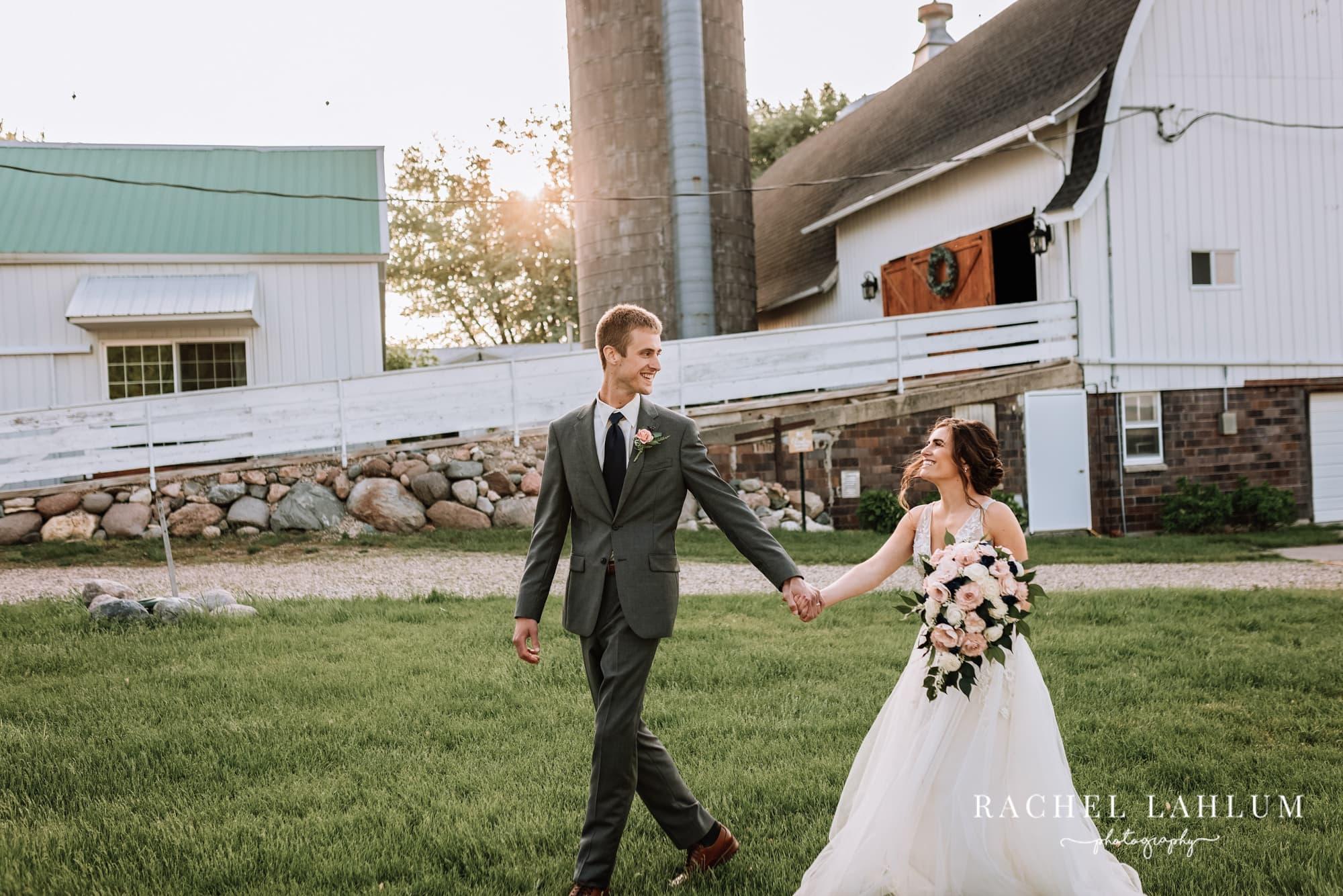Groom walks hand-in-hand with bride at Glencoe, MN, wedding.