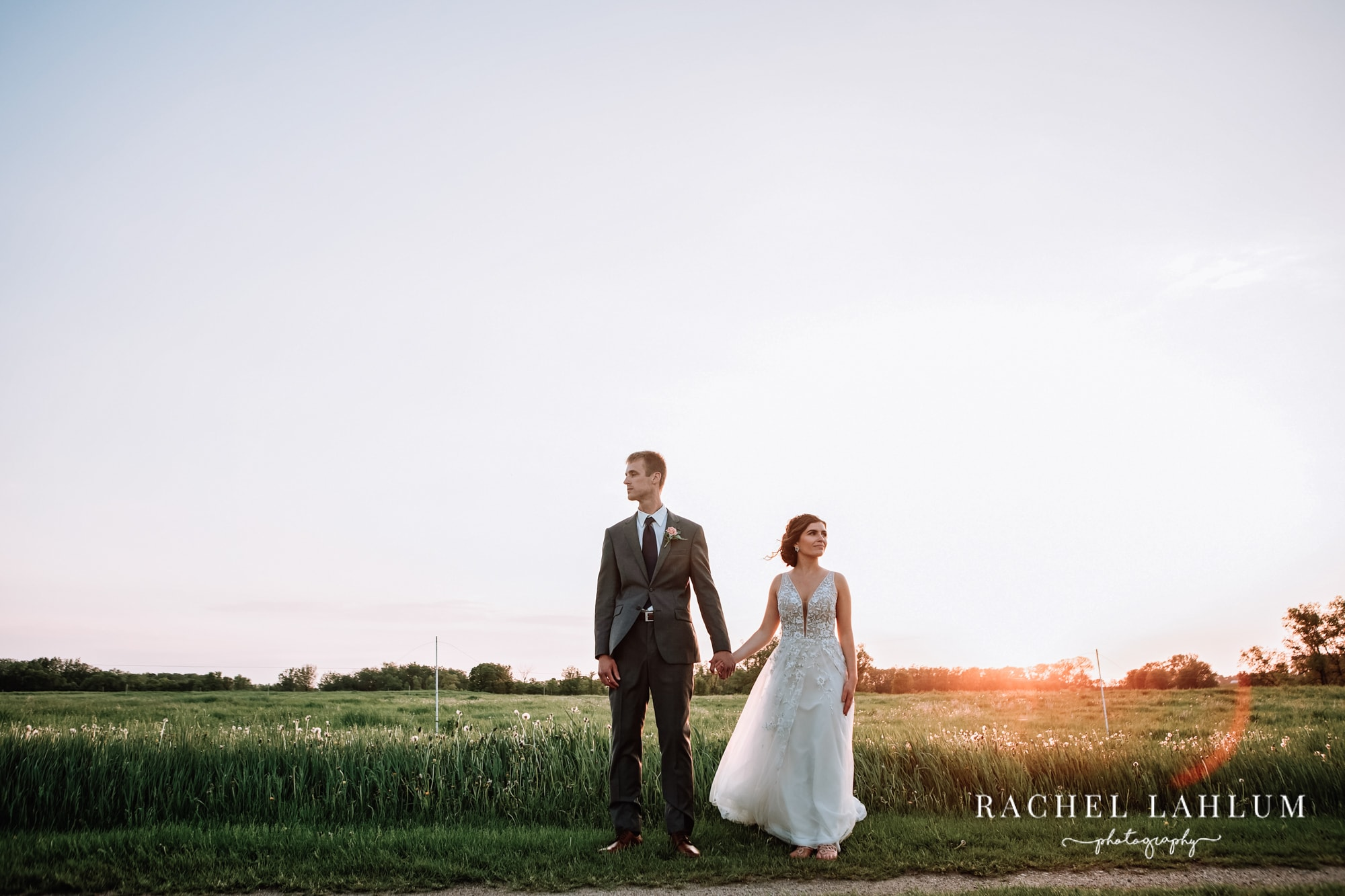 Portrait of bride and groom in front of sunset over pasture at The Cottage Farmhouse wedding venue in Glencoe, Minnesota.