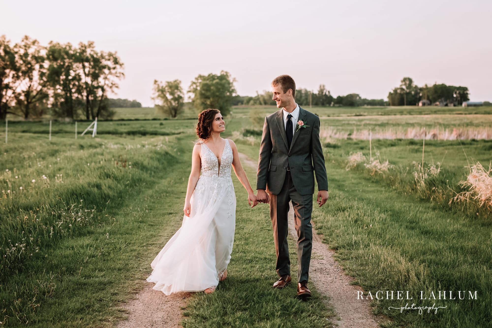 Bride and groom walk down dirt road at The Cottage Farmhouse.