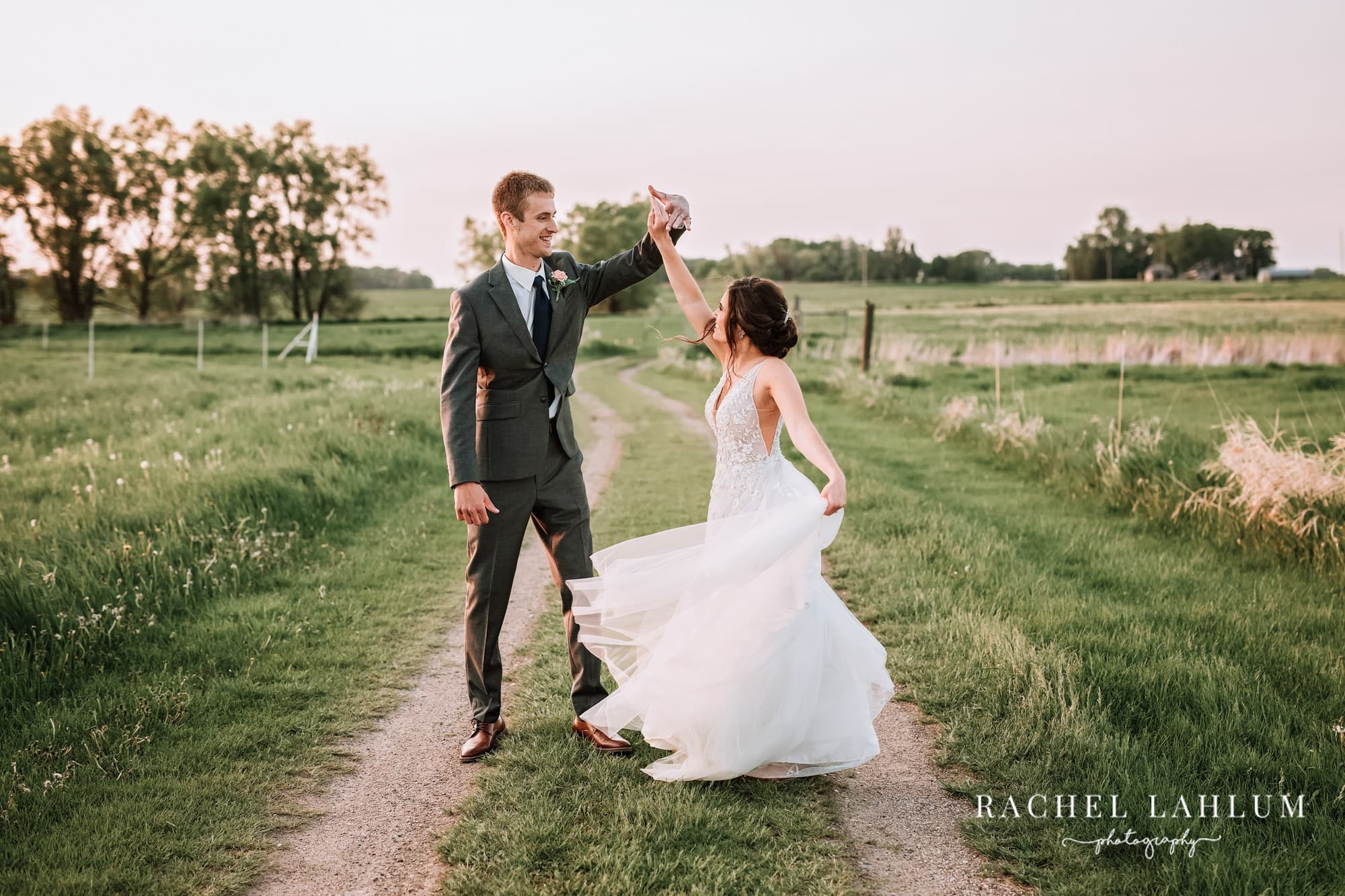 Groom twirls bride on dirt road by The Cottage Farmhouse in Glencoe, MN.