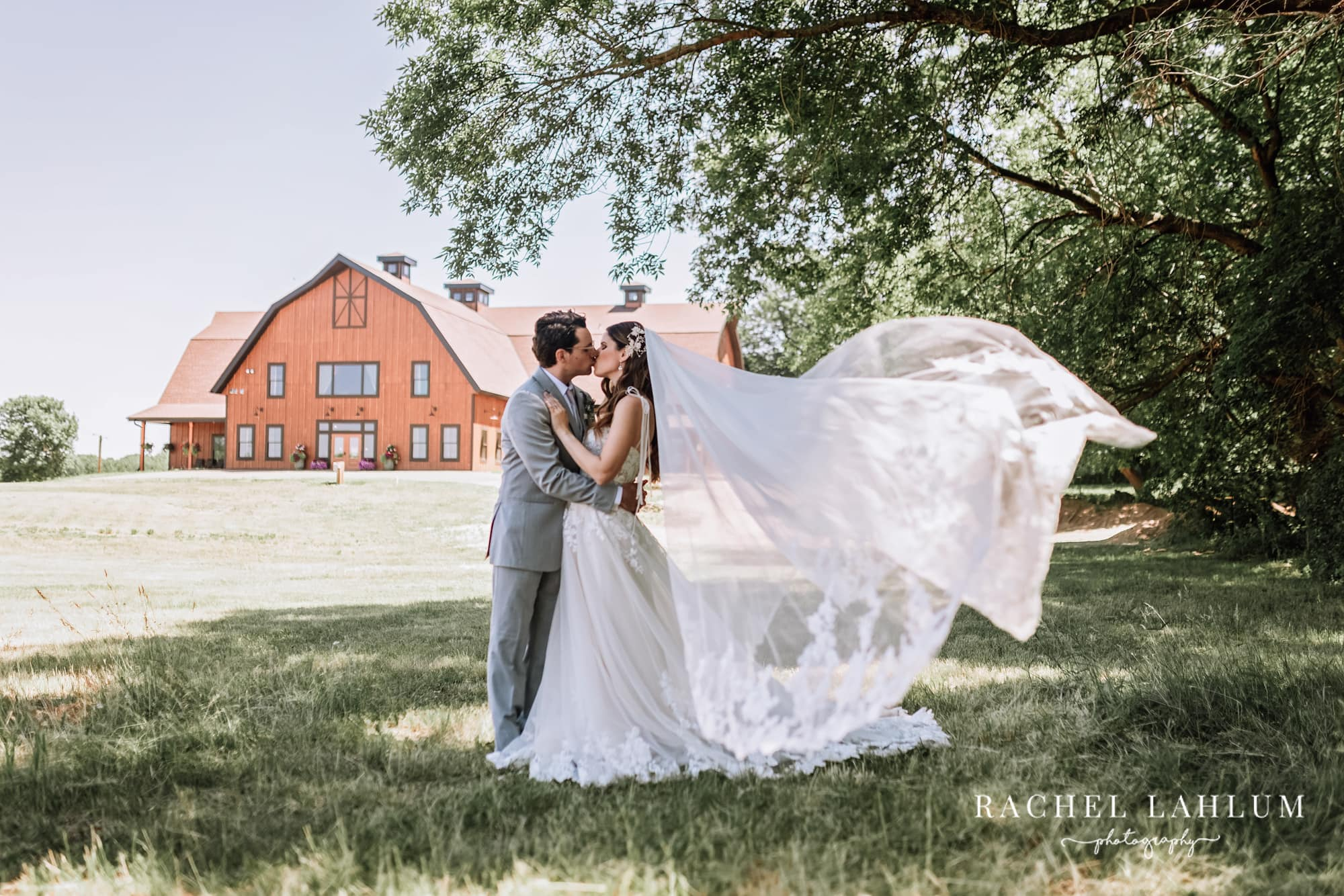 Bride and groom kiss in front of Circle B Ranch at styled wedding photography shoot in Isanti, Minnesota.
