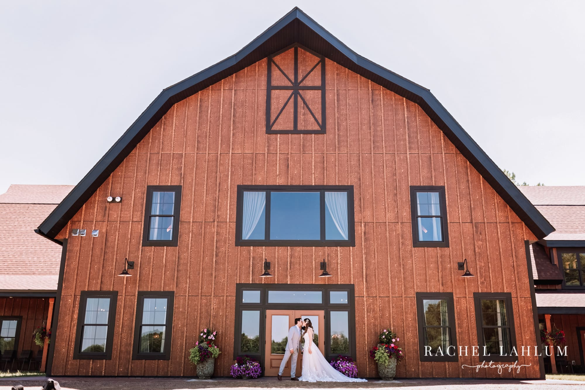 Bride and groom kiss in front of Circle B Ranch's wedding venue in Isanti, Minnesota.