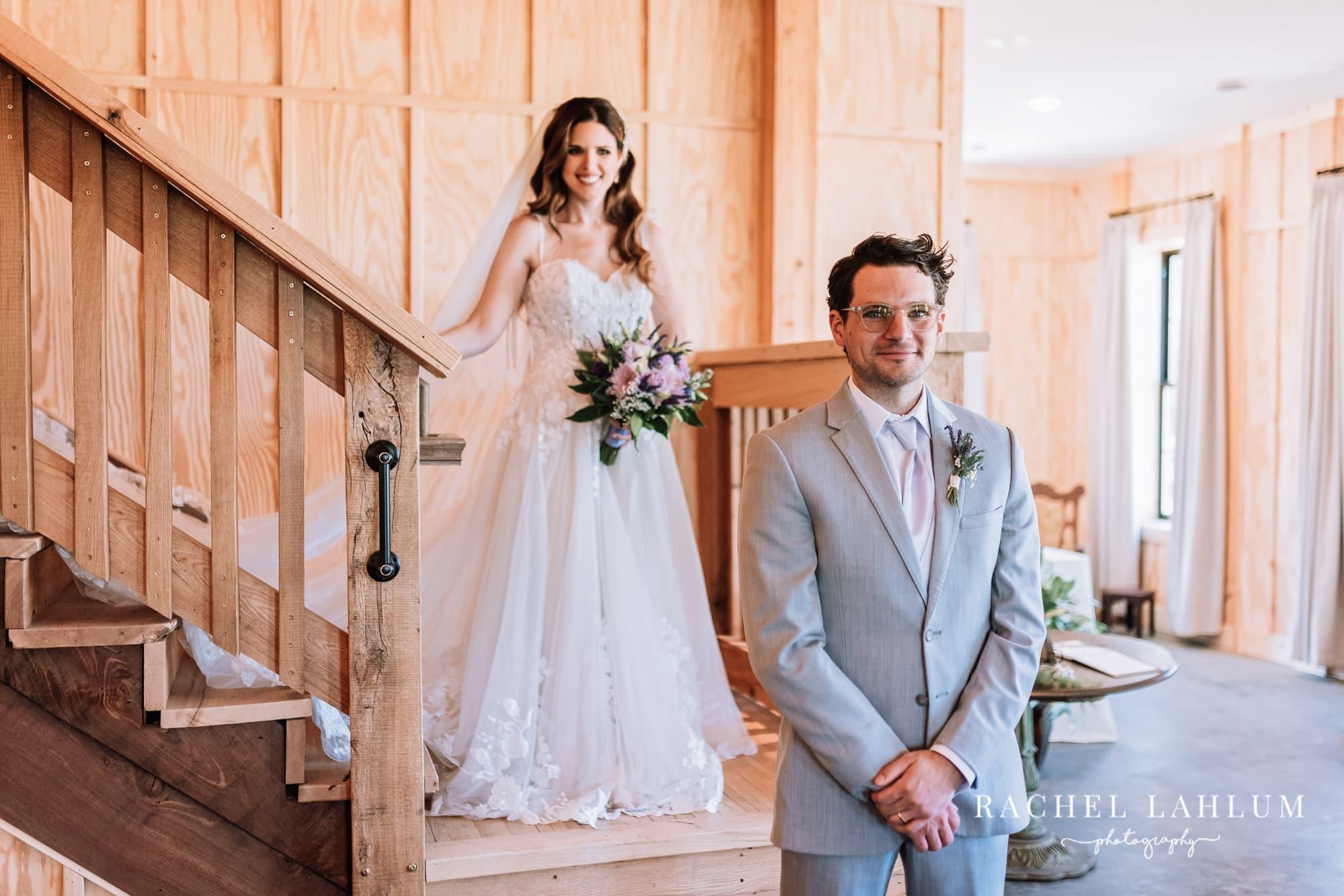 Bride walks up behind groom inside Circle B Ranch in Isanti, Minnesota.