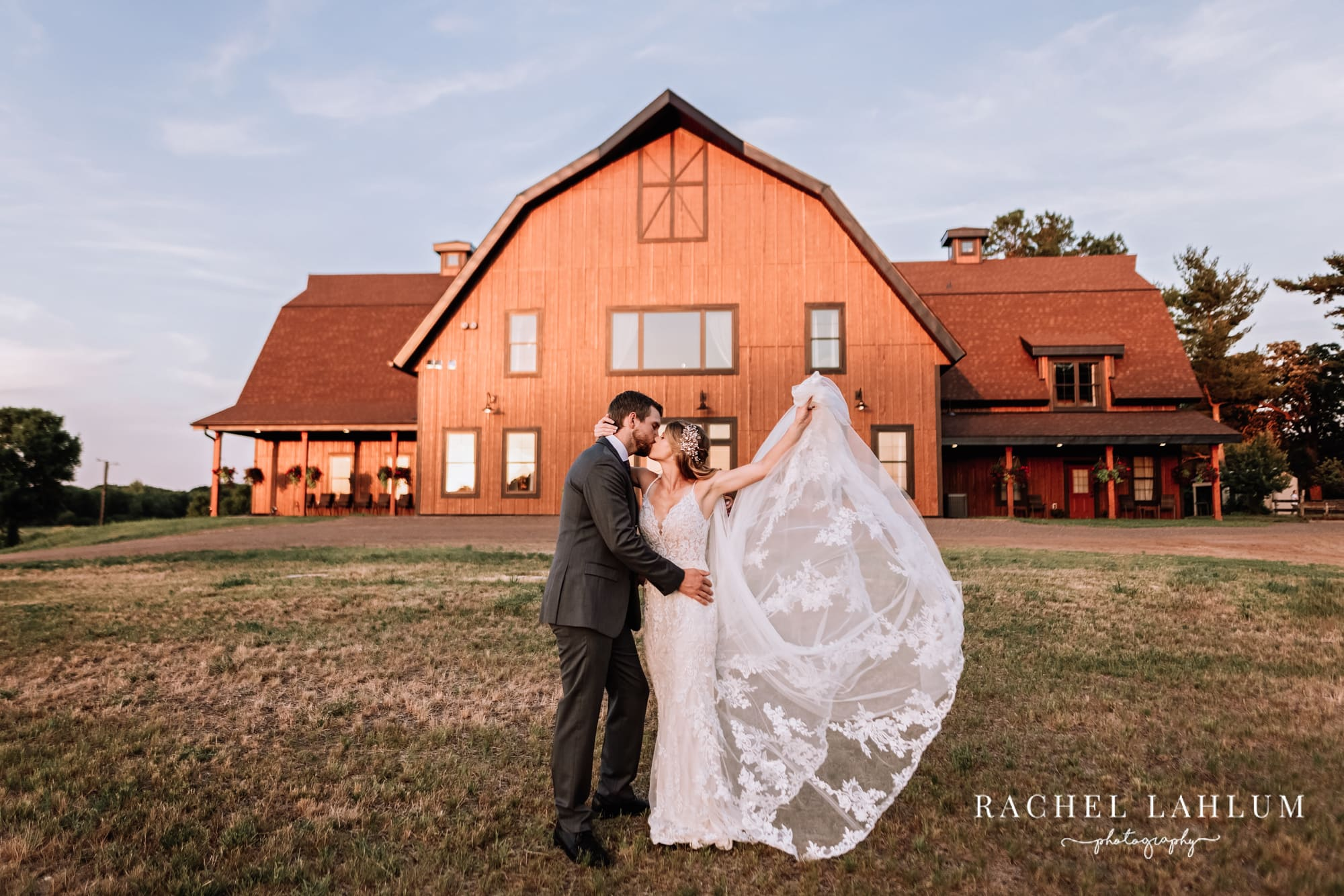 Bride and groom kiss in front of Circle B Ranch during a styled wedding photography shoot in Isanti, Minnesota.