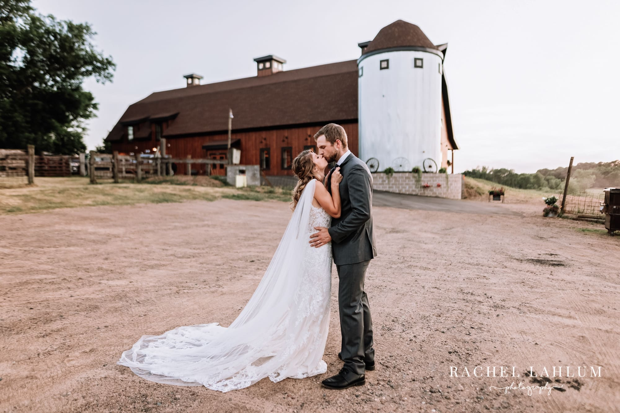 Bride and groom kiss in front of barn-style wedding venue in Isanti, Minnesota.