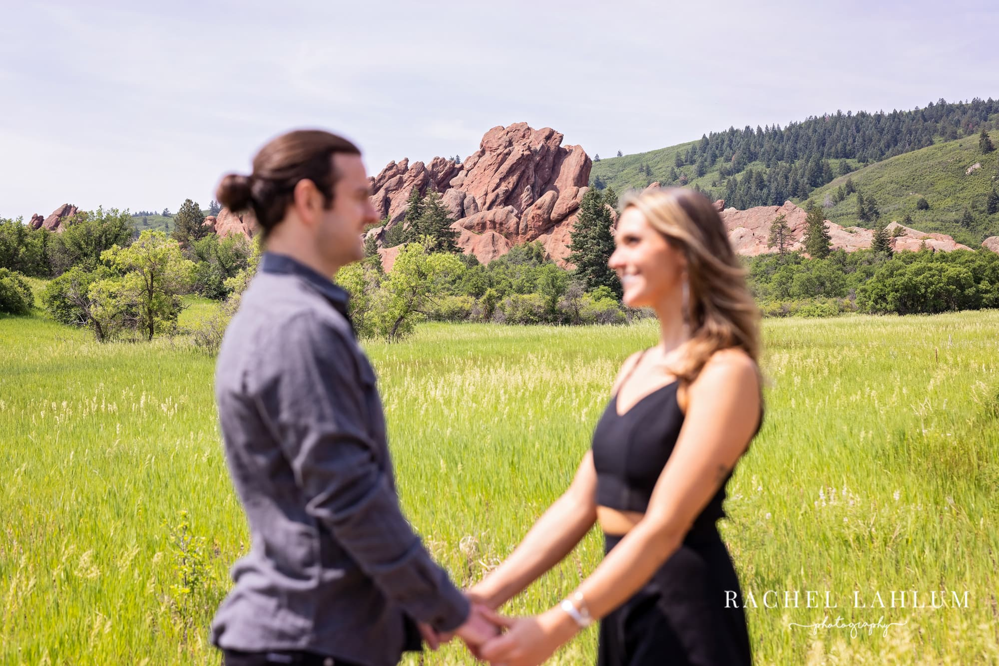 Couple hold hands and look at each other in front of rock formation at Roxborough State Park in Colorado.