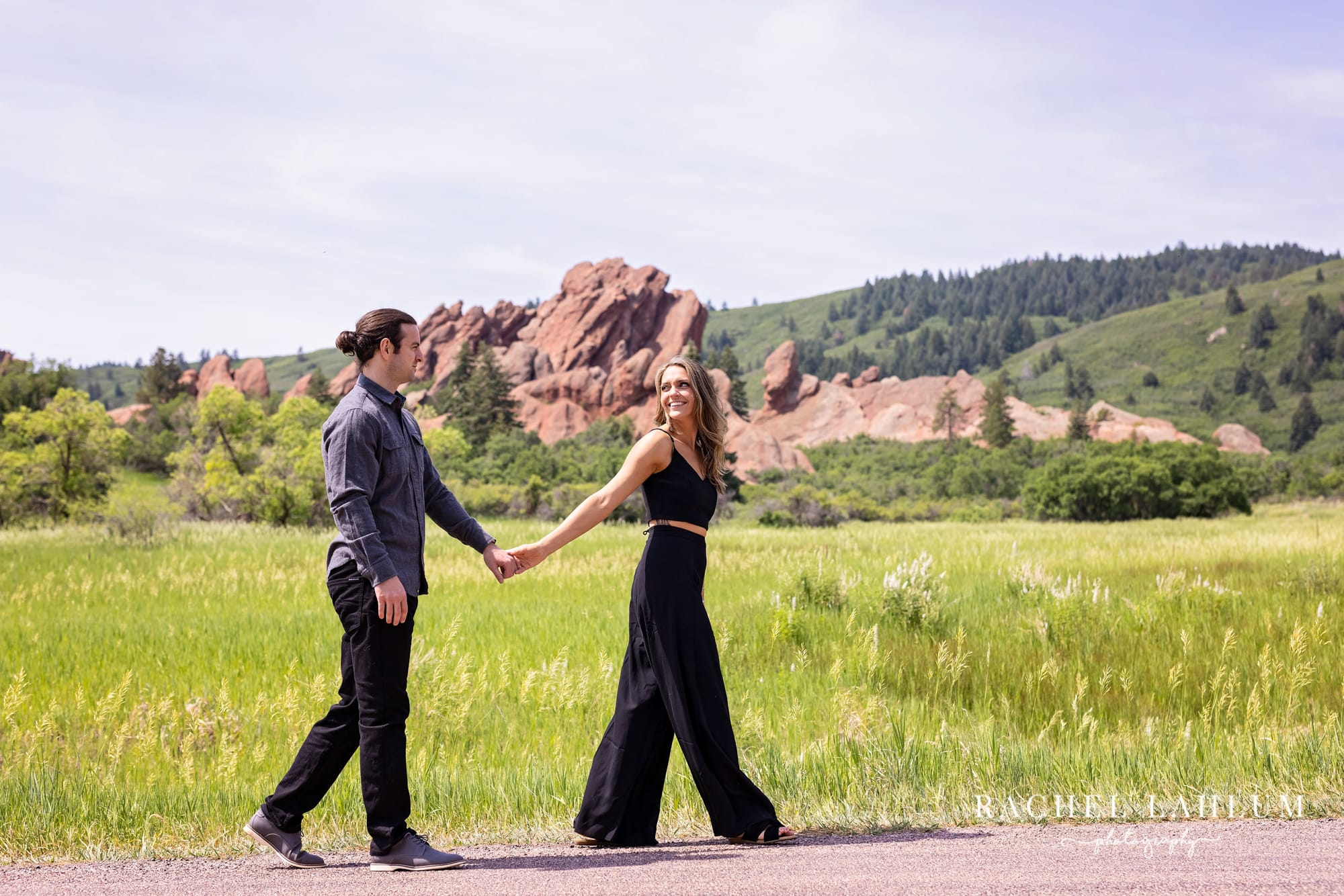Couple hold hands during engagement photography session at Roxborough State Park in Colorado.