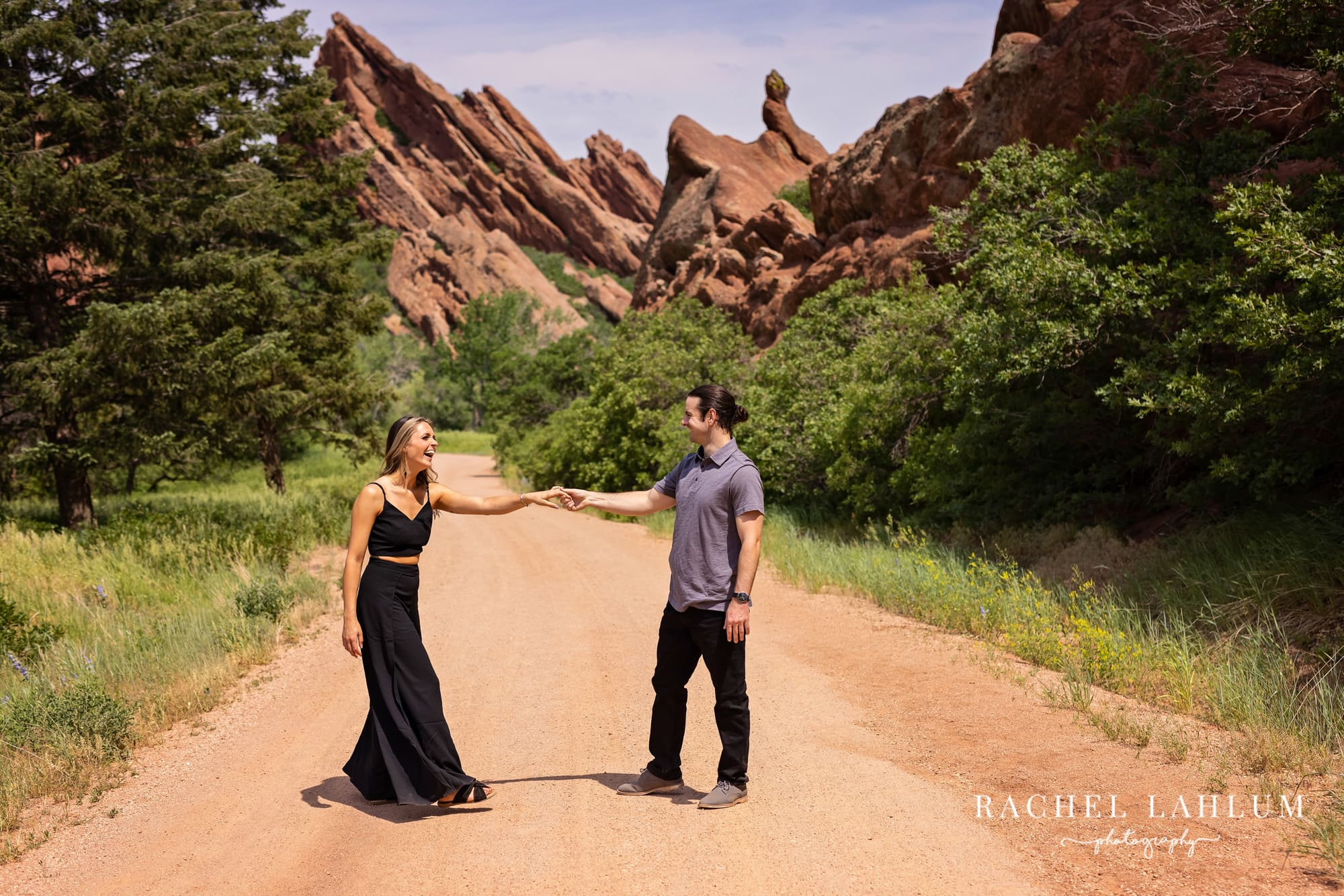 Makayla and Matt stand in road by rock formation in Roxborough State Park in Colorado.