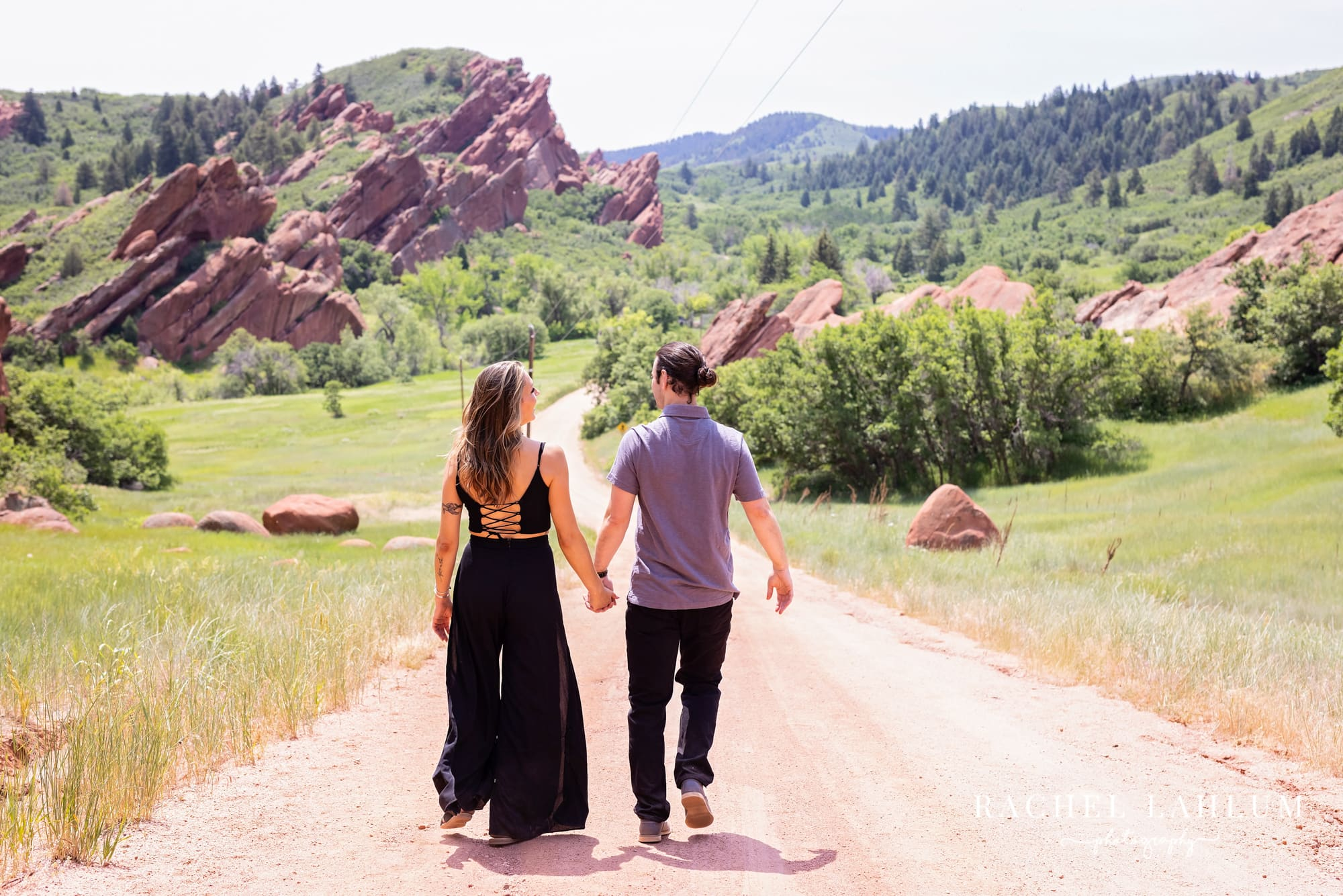 Couple walk down trail for engagement session in Roxborough State Park in Colorado.