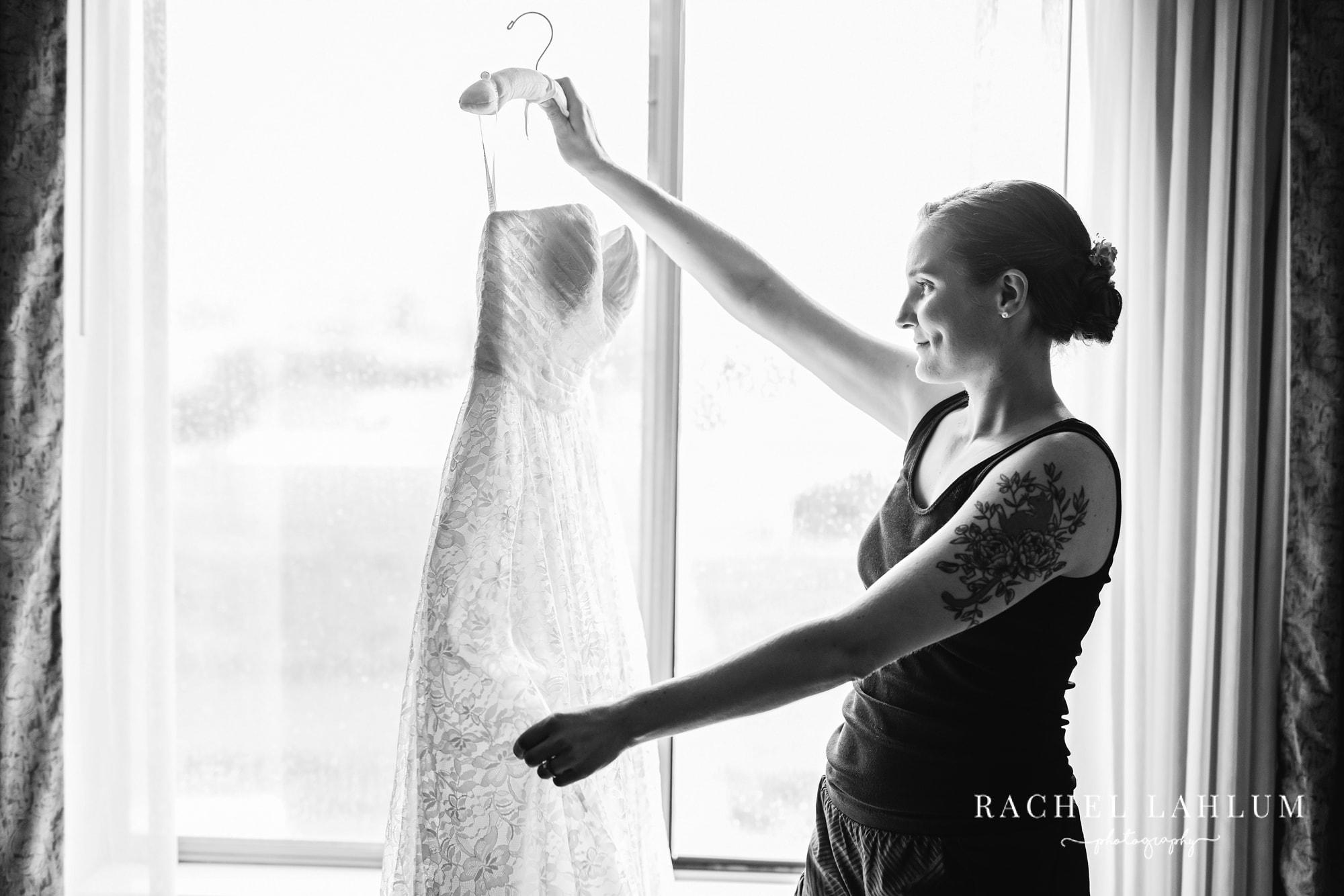 Portrait of bride holding up dress on hanger before wedding at Cedar Creek Barn in Winona, Minnesota.