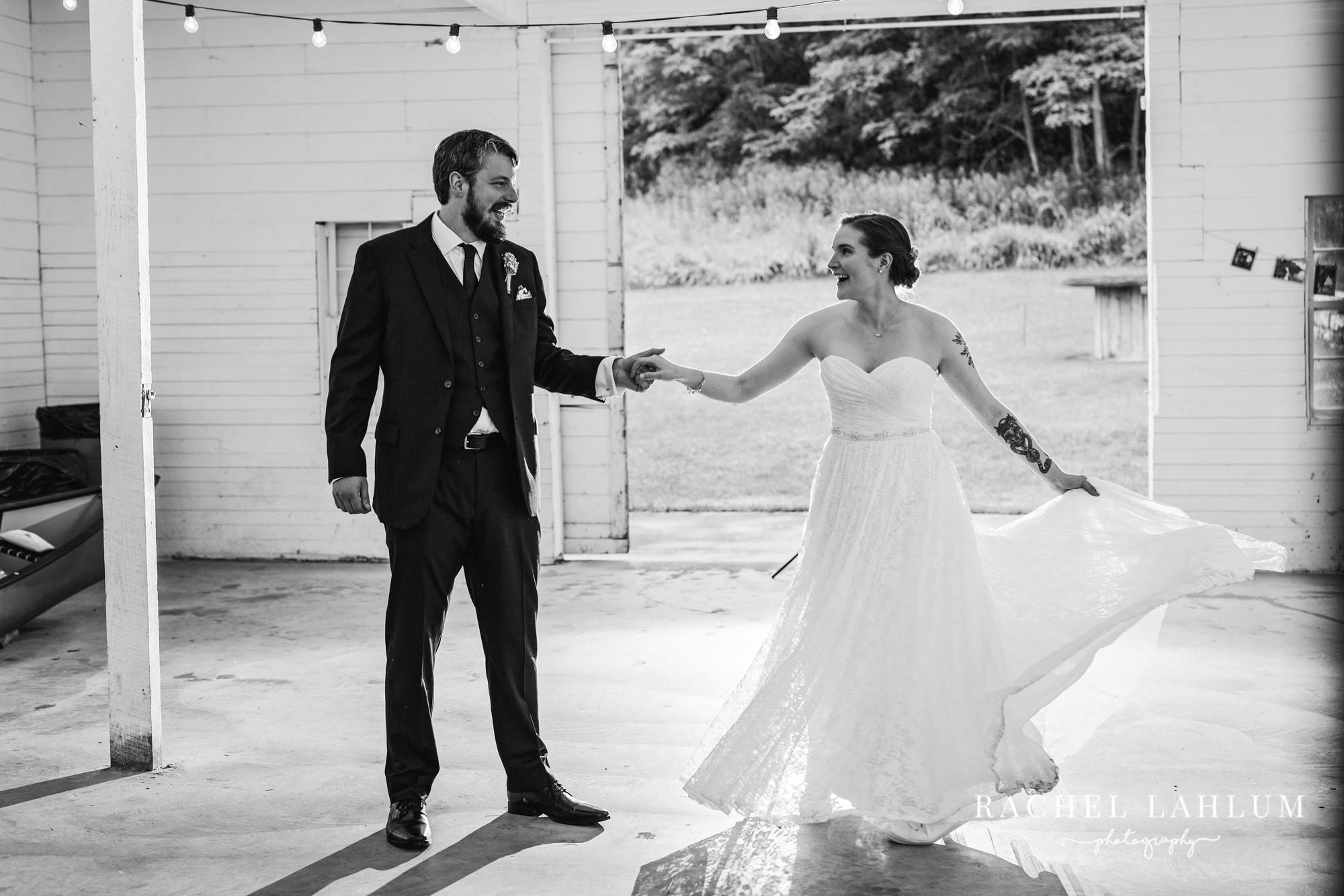 Bride in groom enter the cedar Creek Barn wedding venue in Winona, Minnesota.