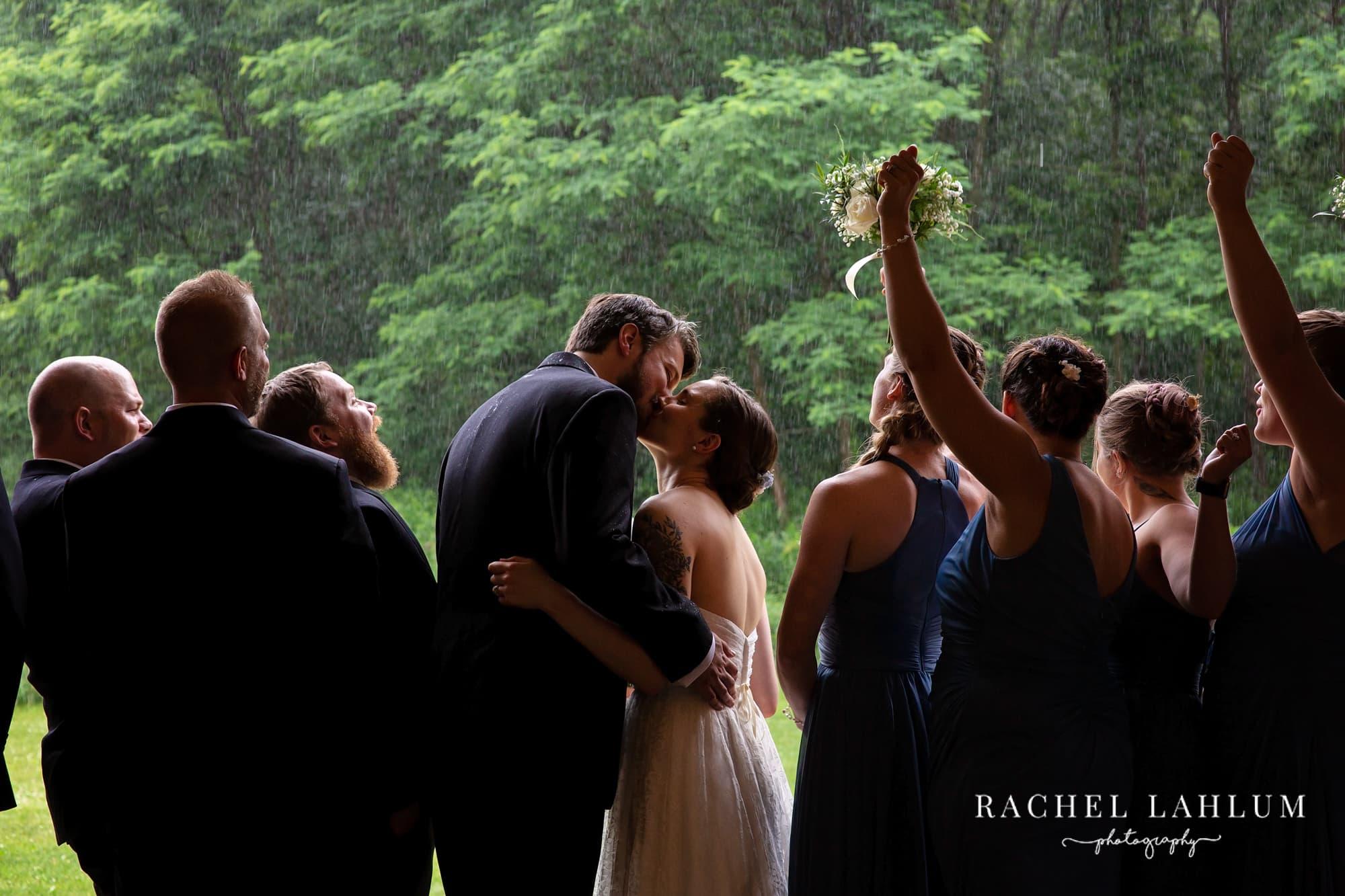 Wedding couple kiss in the rain before in the entrance of Cedar Creek Barn.
