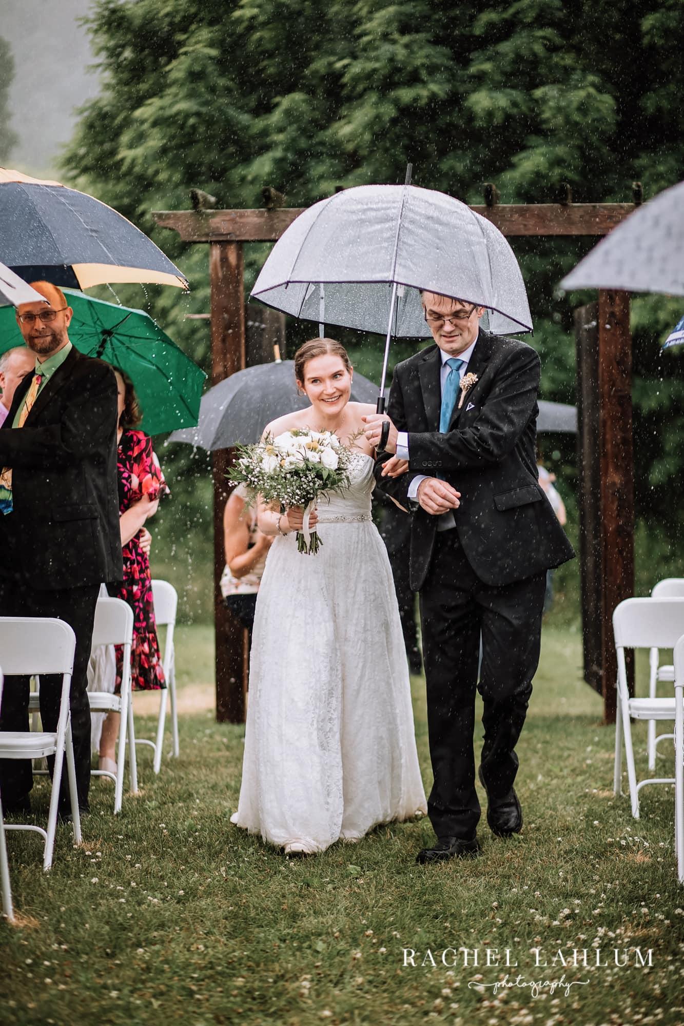 Father walks bride down the aisle under an umbrella during a downpour at Cedar Creek Barn.